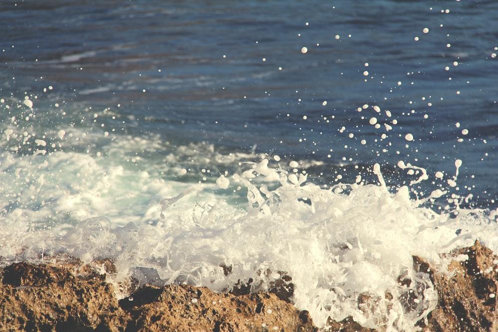 photo of sea wave bump into boulder