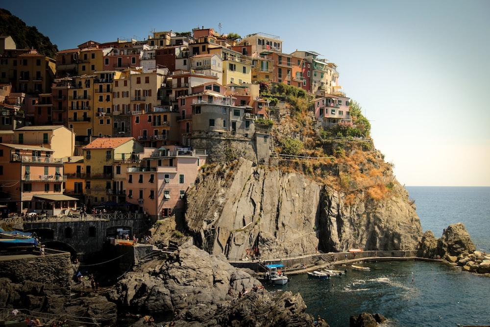 houses on cliff beside ocean during daytime