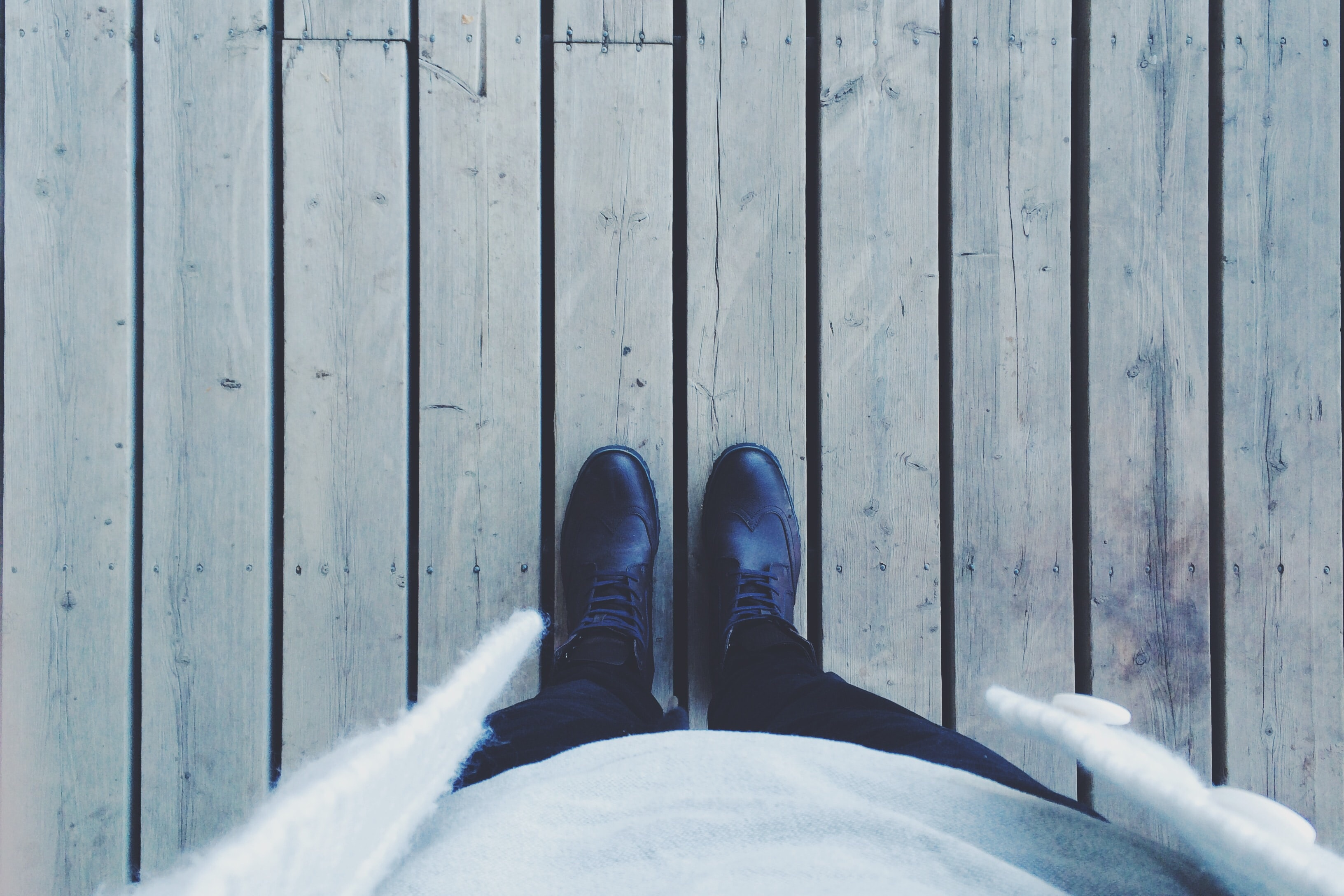 Looking down at the feet of a person wearing black shoes on a boardwalk