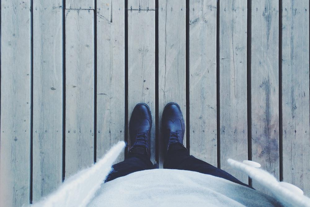 person standing on gray wooden floor