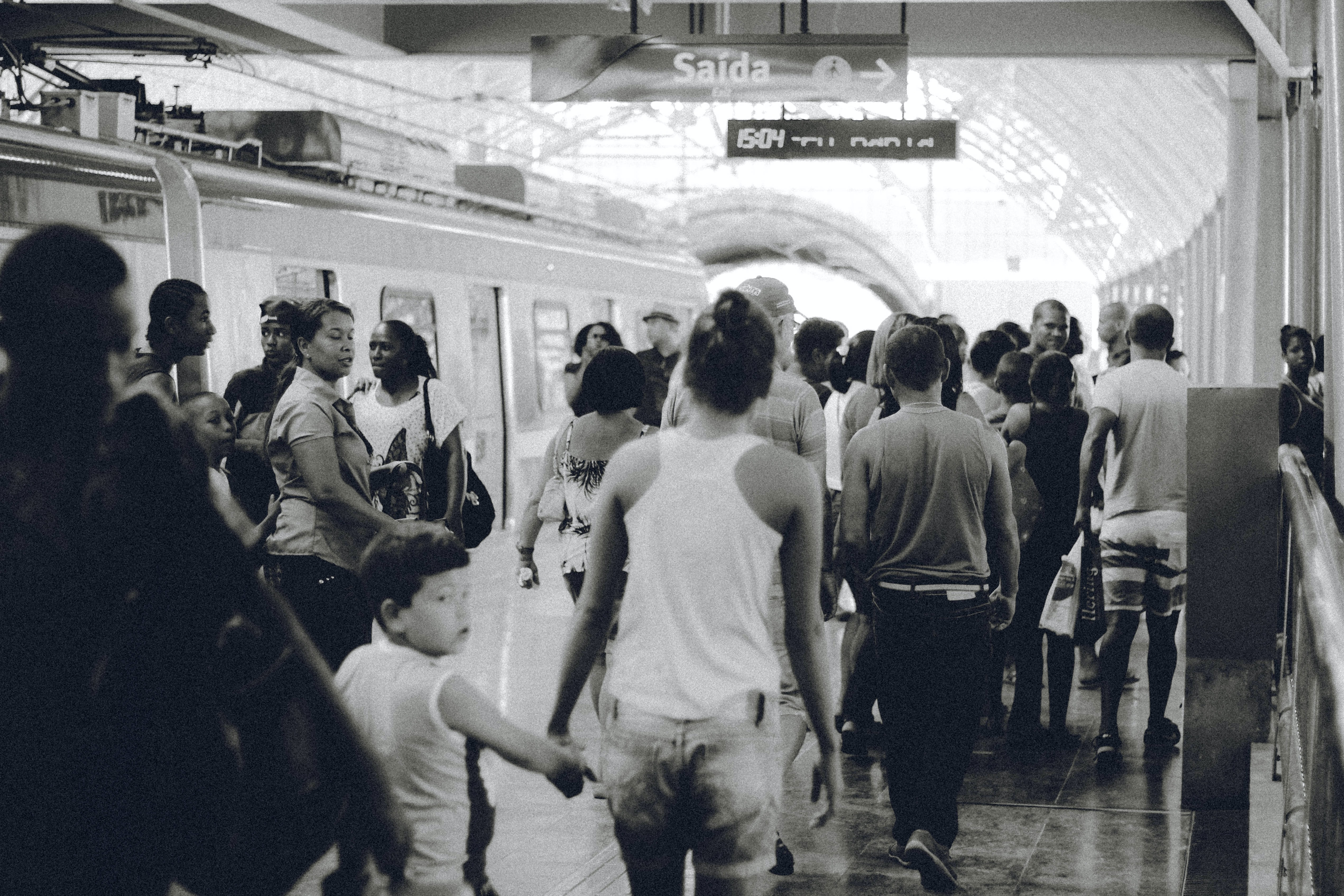 grayscaled photo of crowd on subway