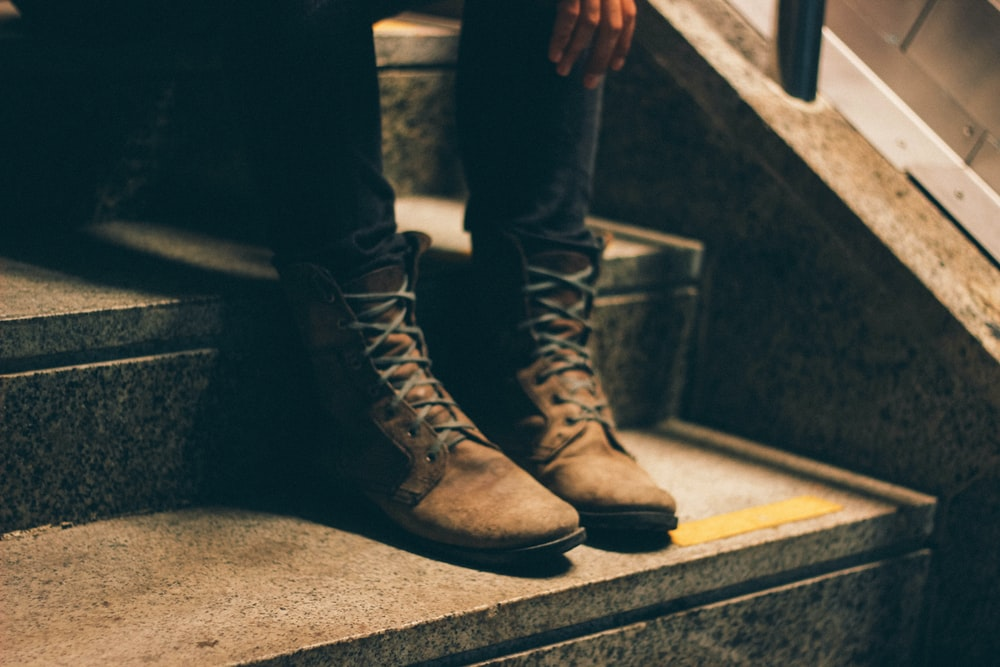 person wearing pair of brown lace-up boots with sitting on stairs