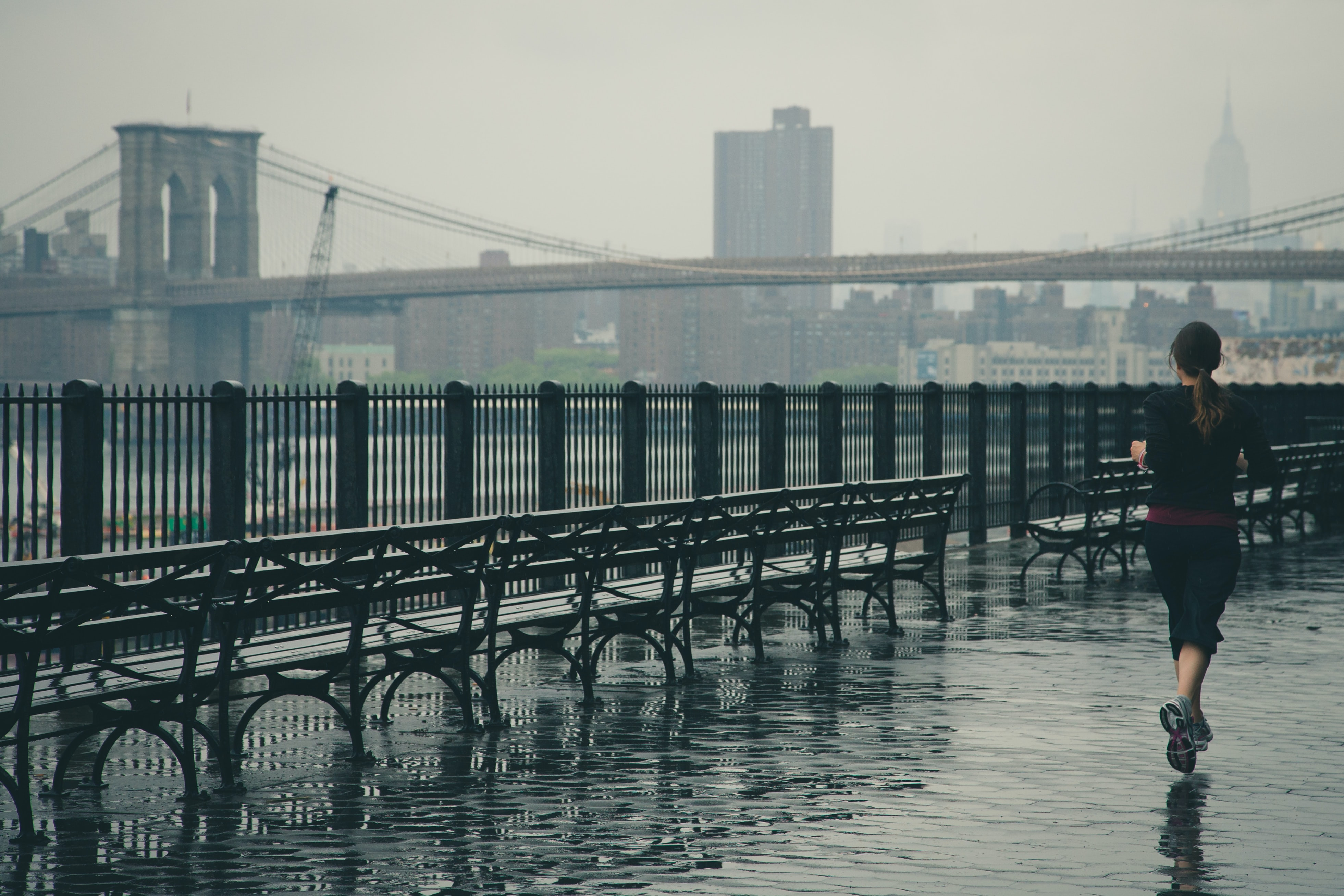 woman running near the body of water with Brooklyn Bridge in the background