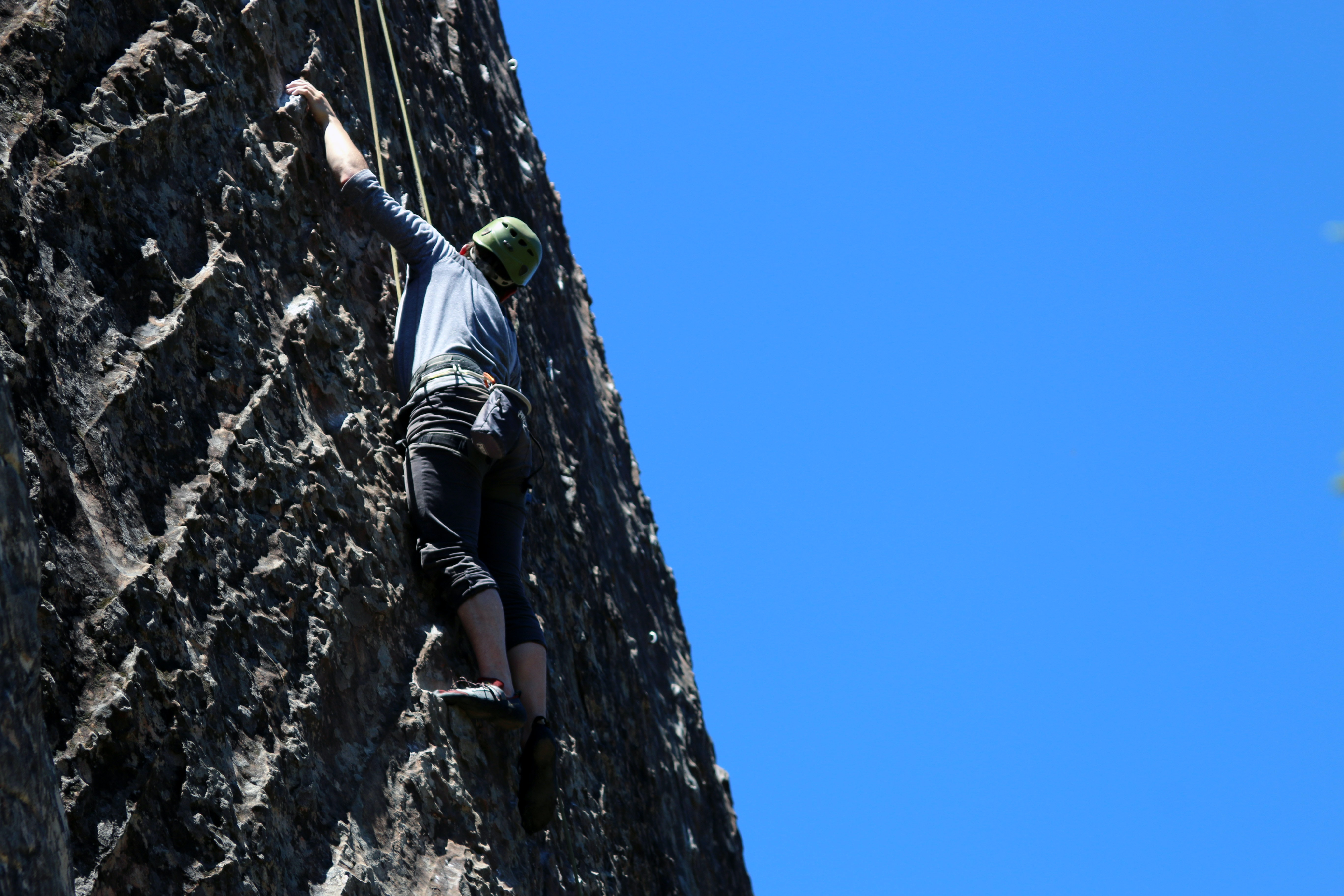 A man rock climbing outdoors on a mountain on a nice day with blue skies