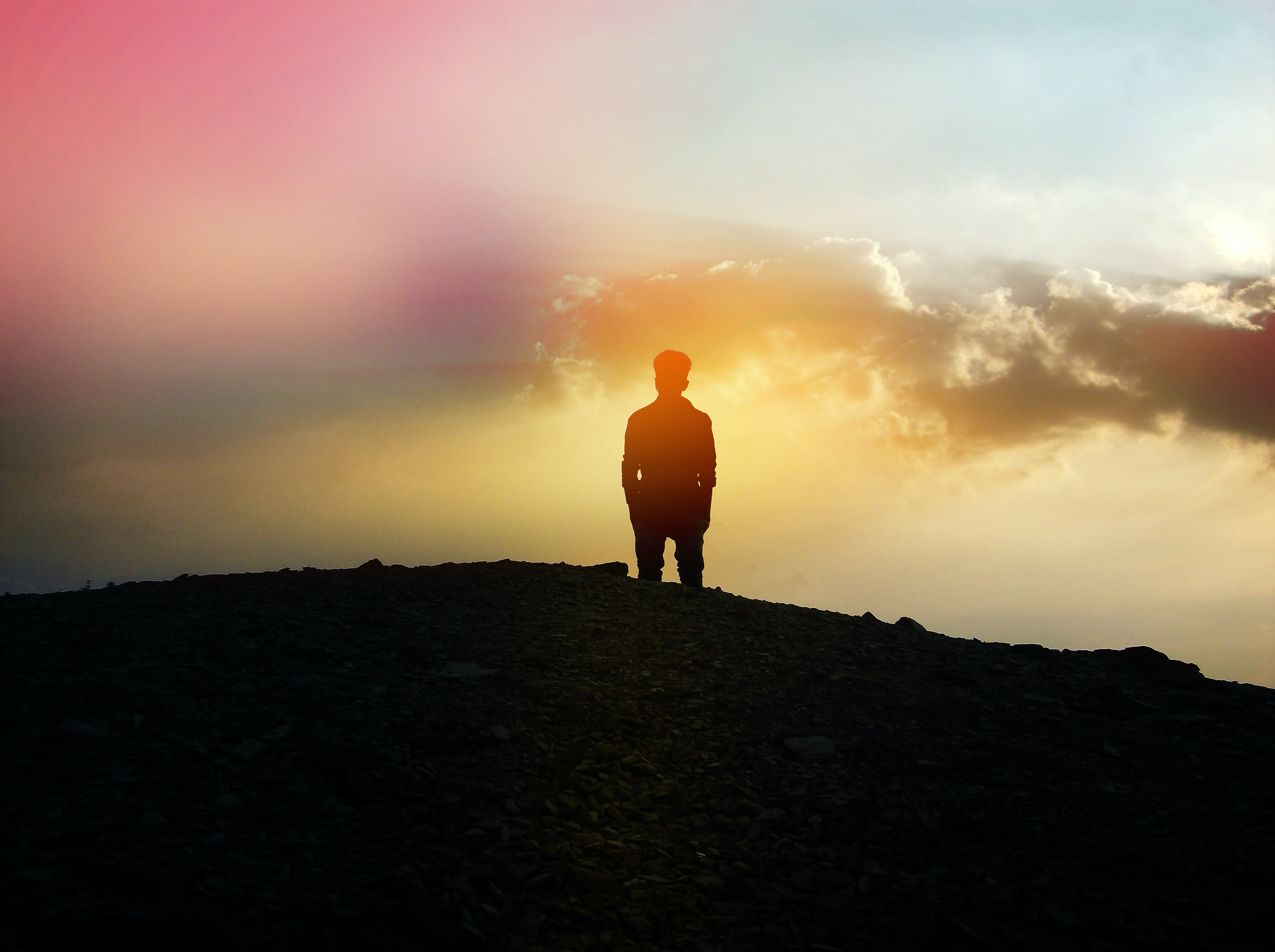The silhouette of a man standing on a mountain looking out into the pink and yellow sky during sunset