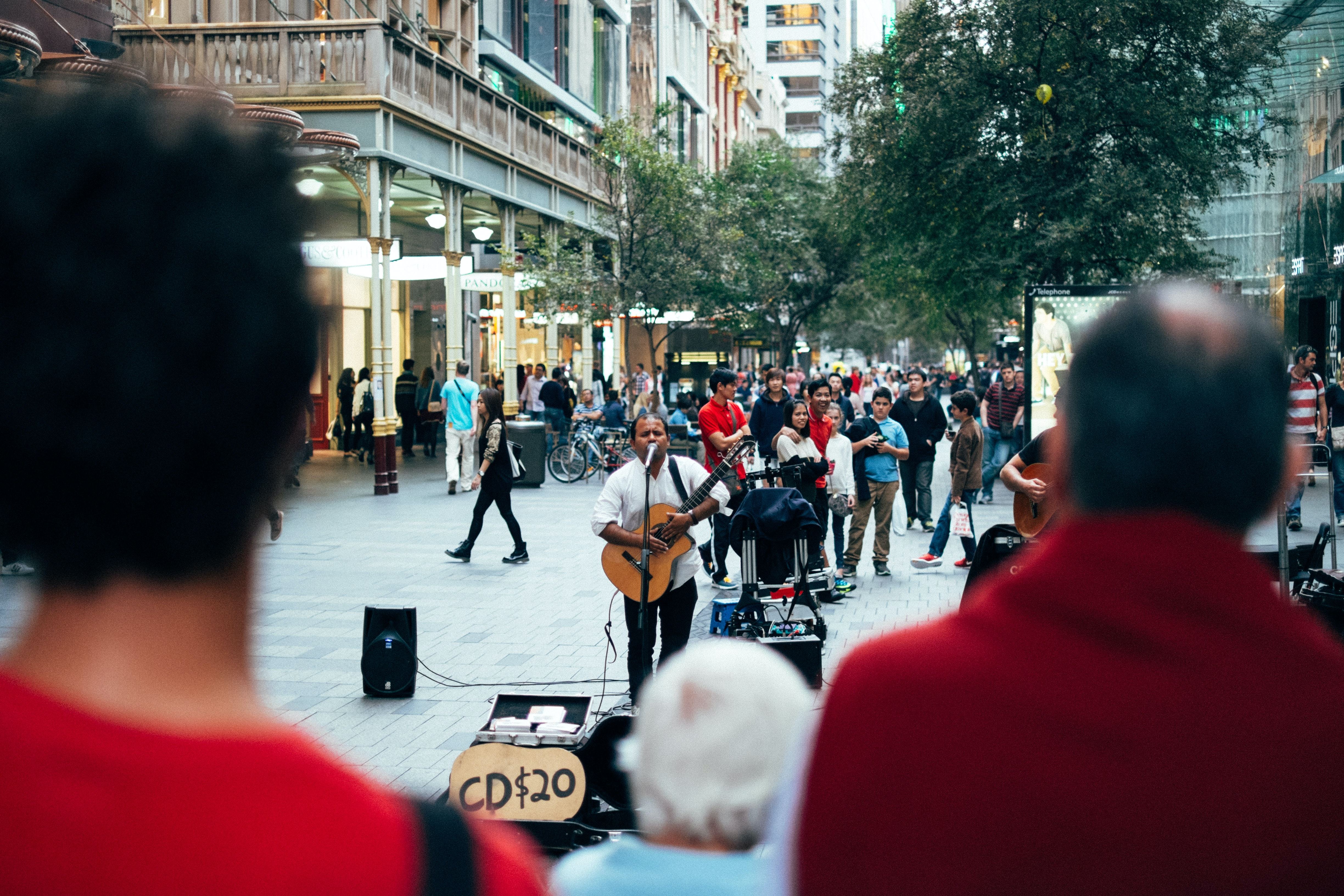 """A male guitar player busking on a crowded street with a sign reading """"CD $20"""""""