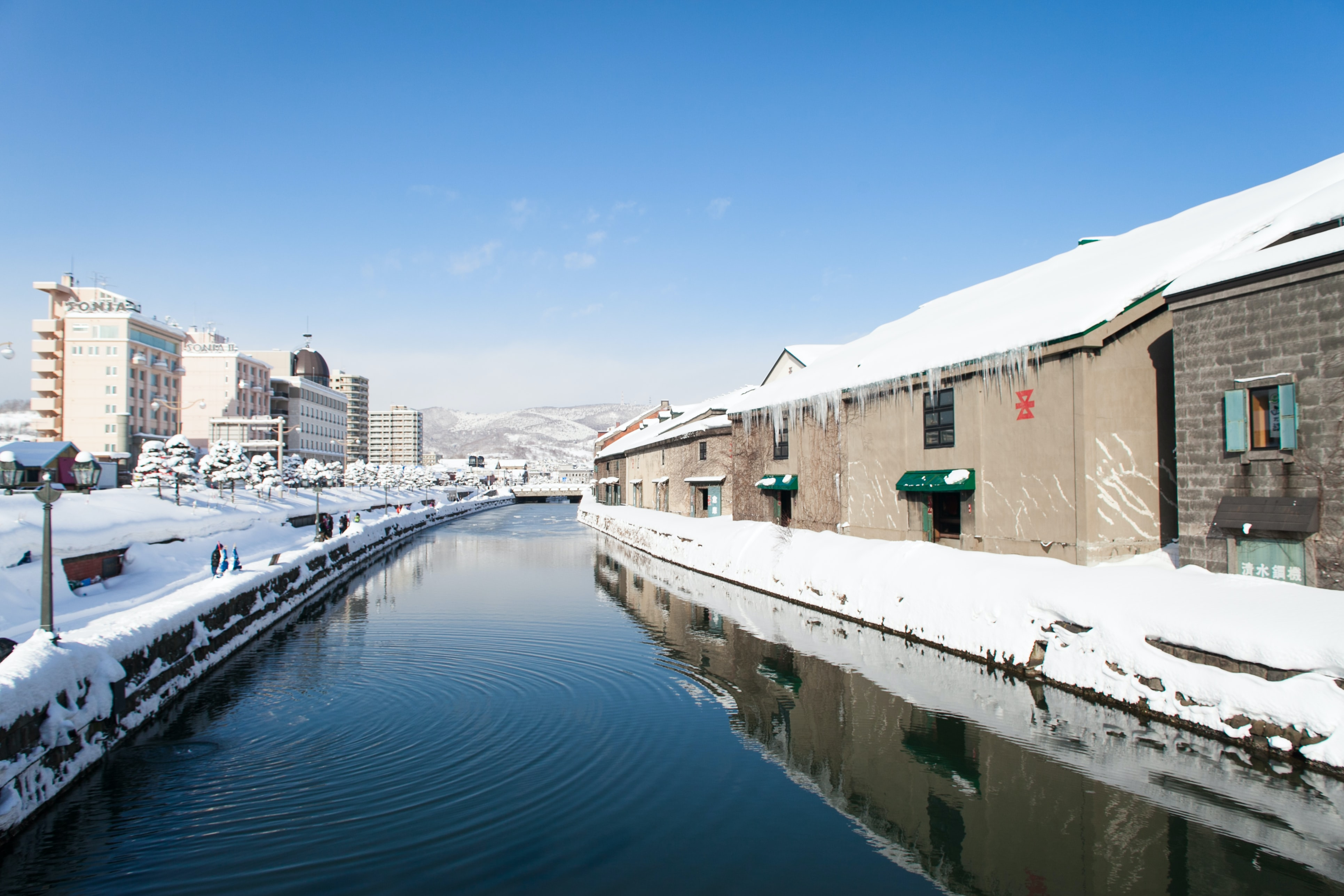 The canal during winter flanked by snow covered buildings