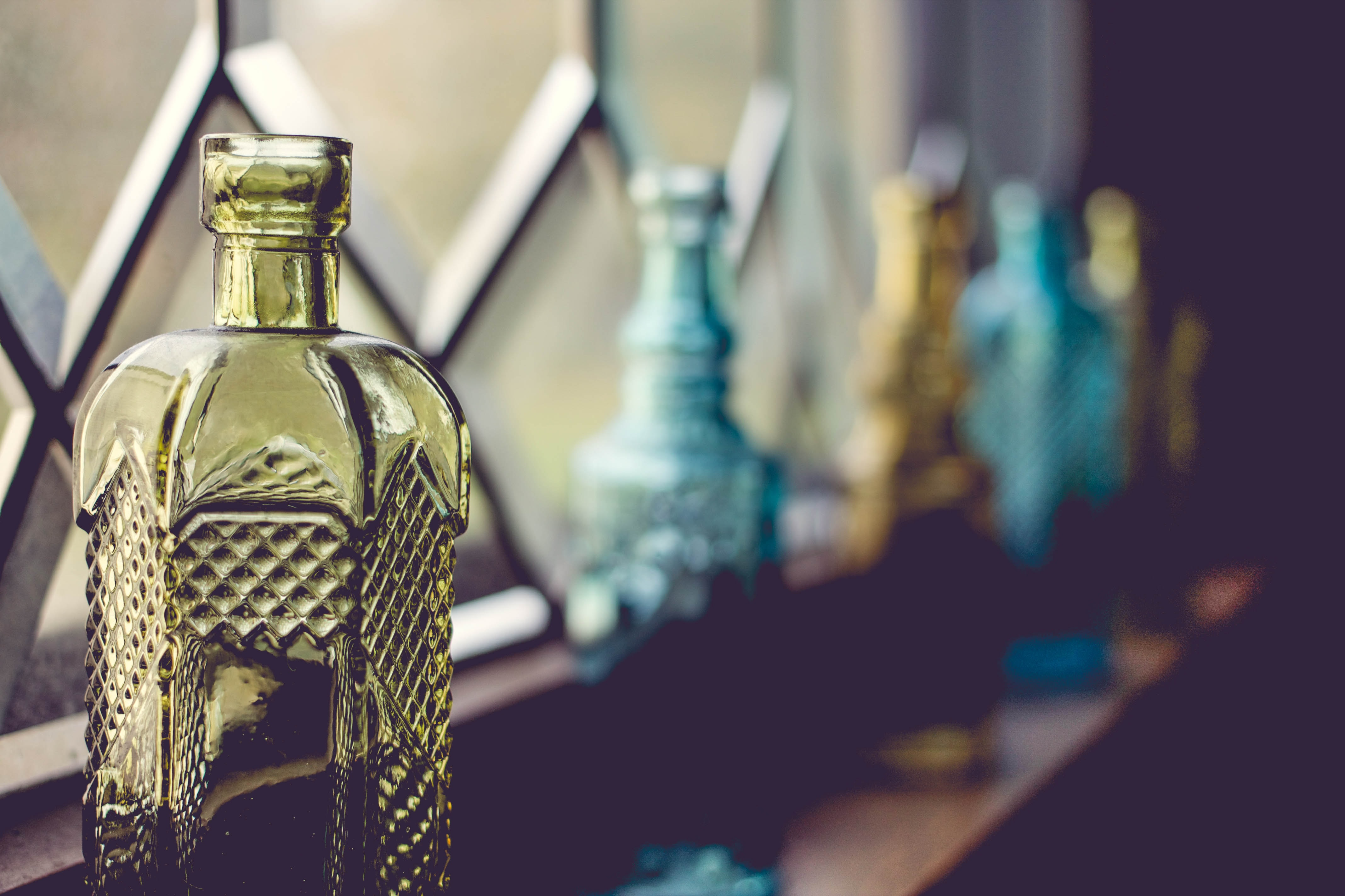 Antique bottles in front of a window and decorative glass panes