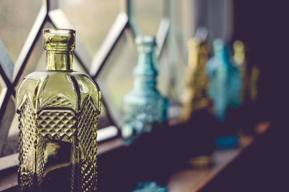 shallow focus photography of yellow glass bottle beside window