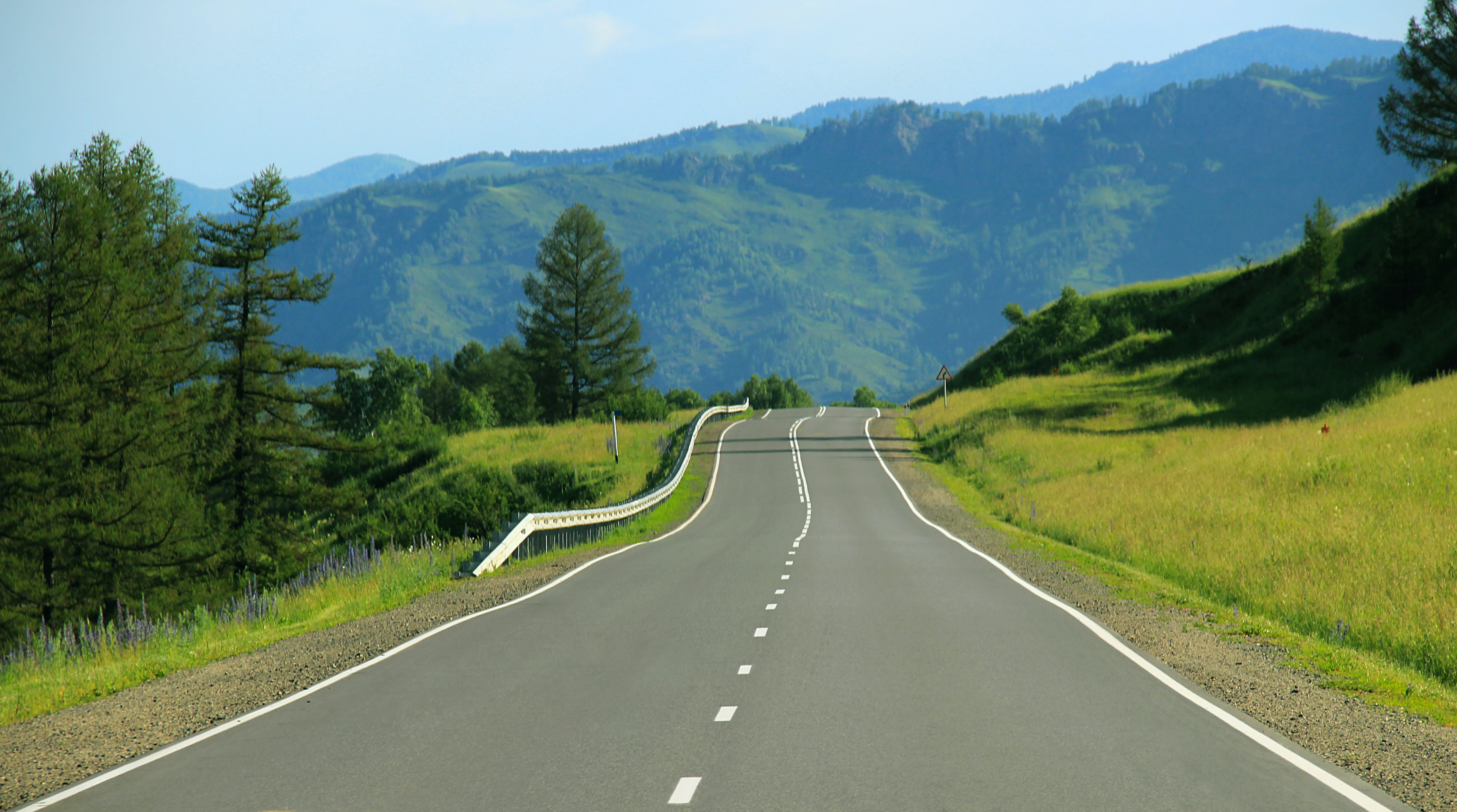 An empty road around green grassy hills on a sunny day