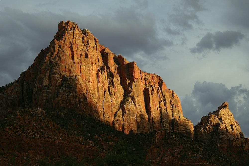 brown mountain under gray sky