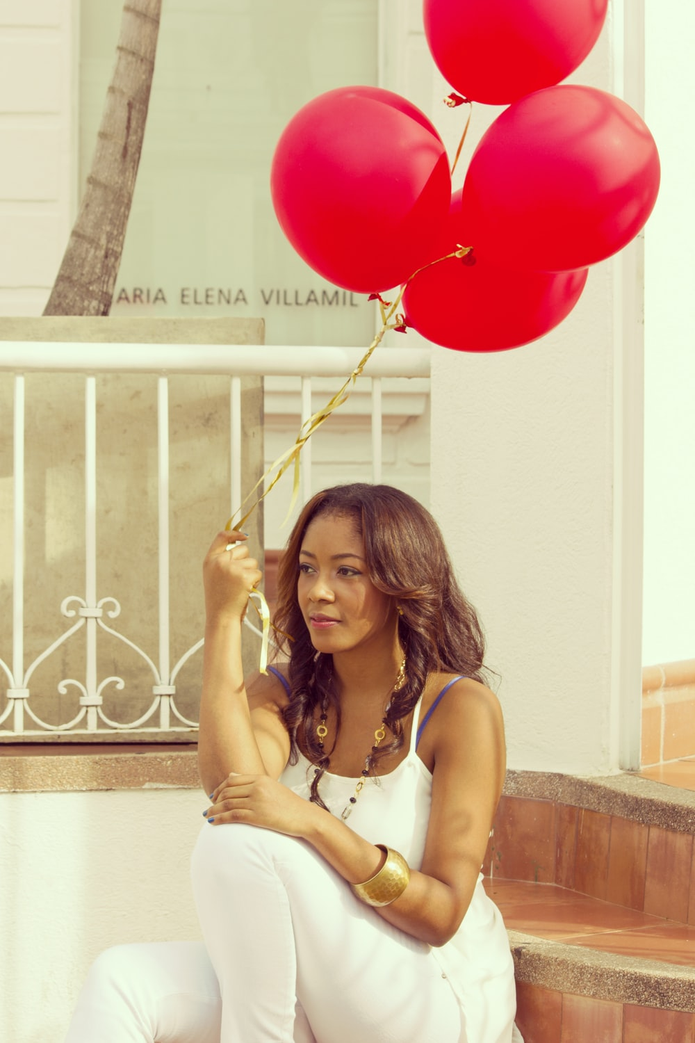 woman sitting on staircase while holding red balloons