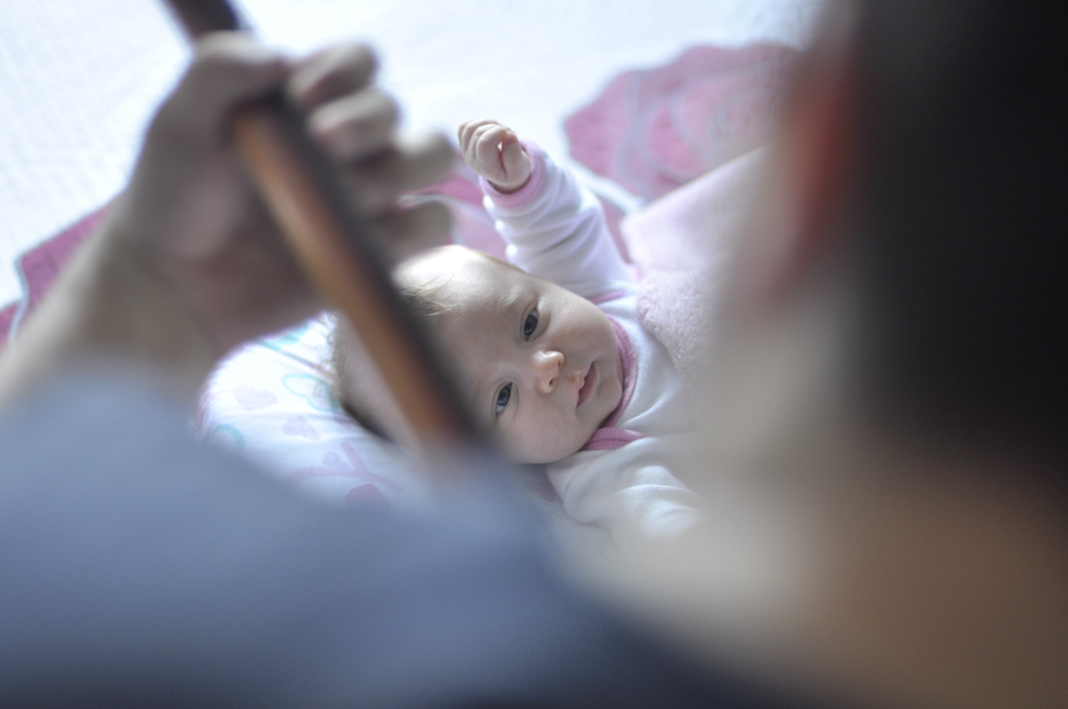 A father plays guitar for his baby, who lays on the bed watching.