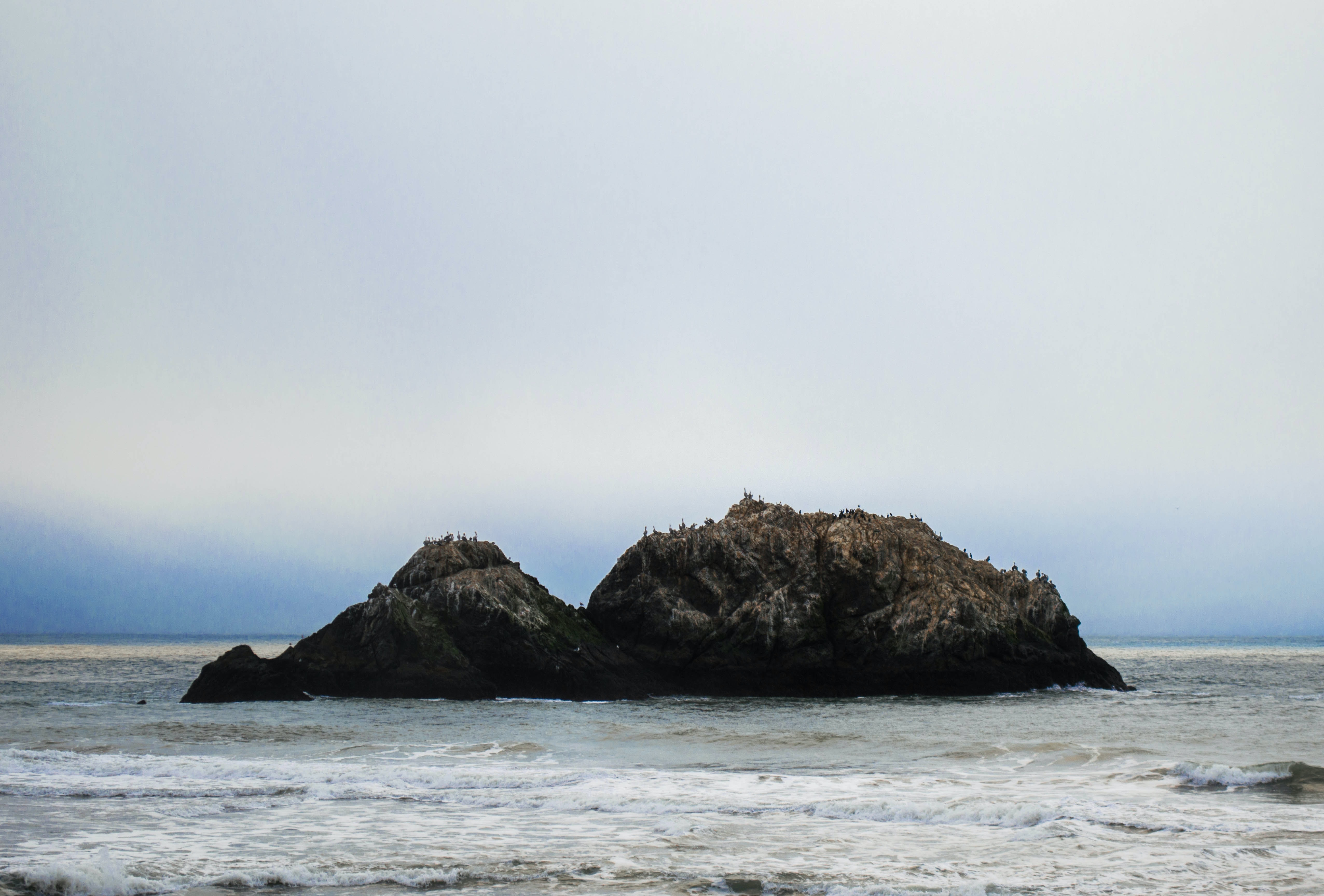 A rocky outcrop in the middle of a rough see