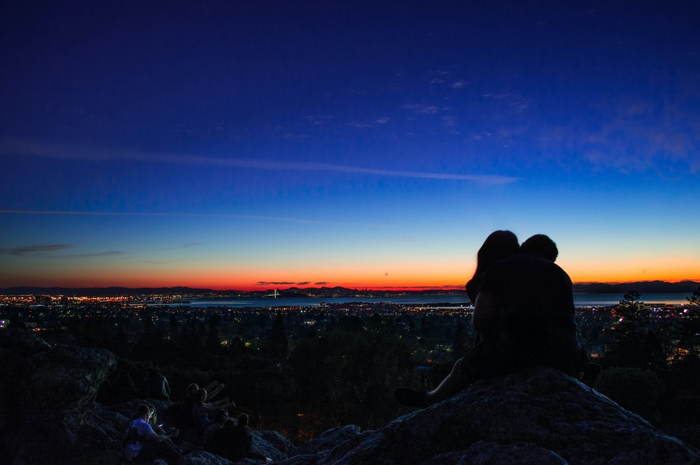 Couple in silhouette kisses atop a rocky hill, a city and sunset pictured in the background