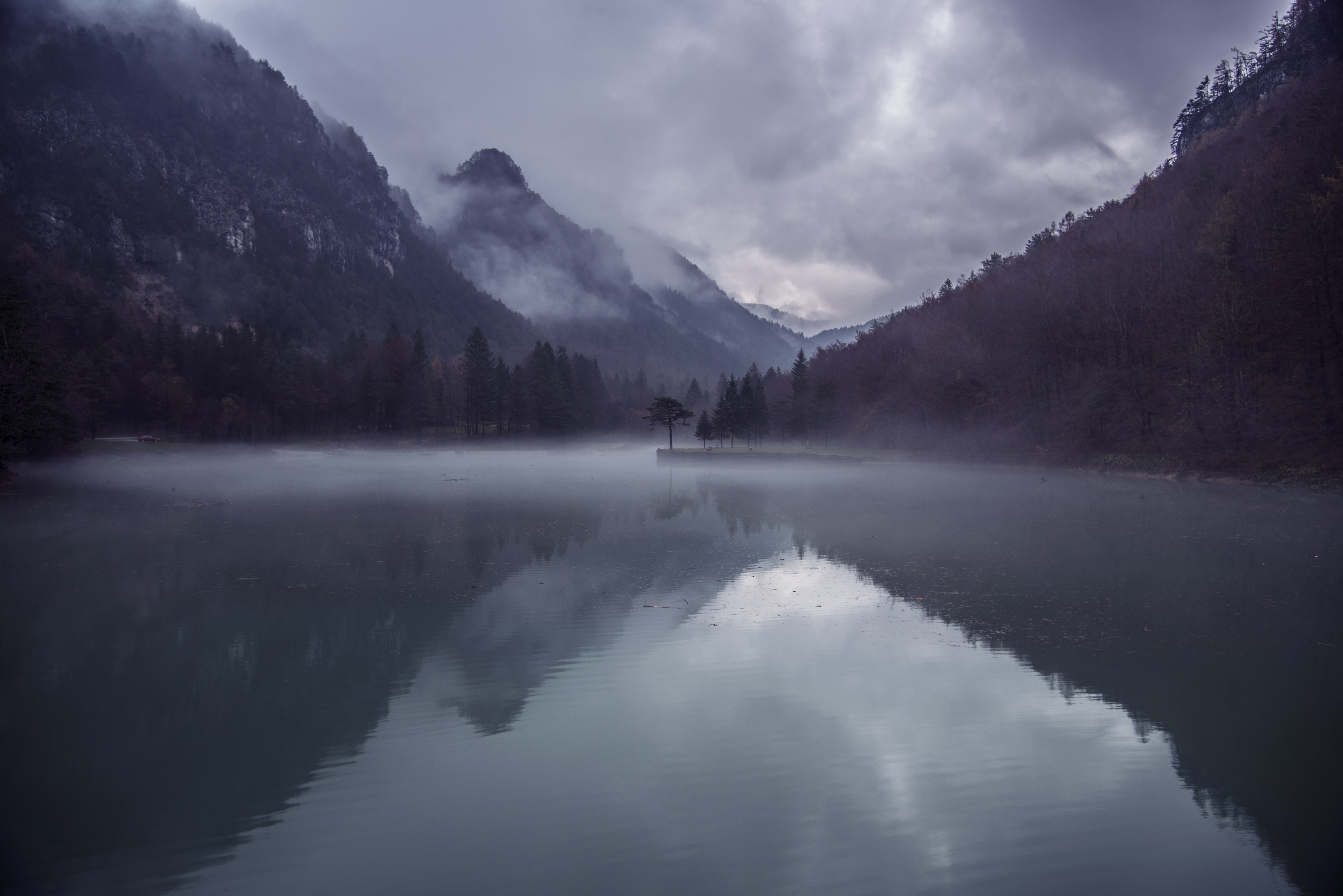 A view from the reflective surface of a lake on wooded mountains shrouded in clouds