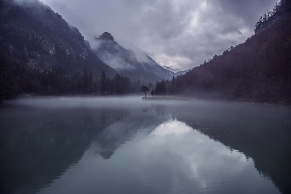 body of water surrounded by mountain during daytime