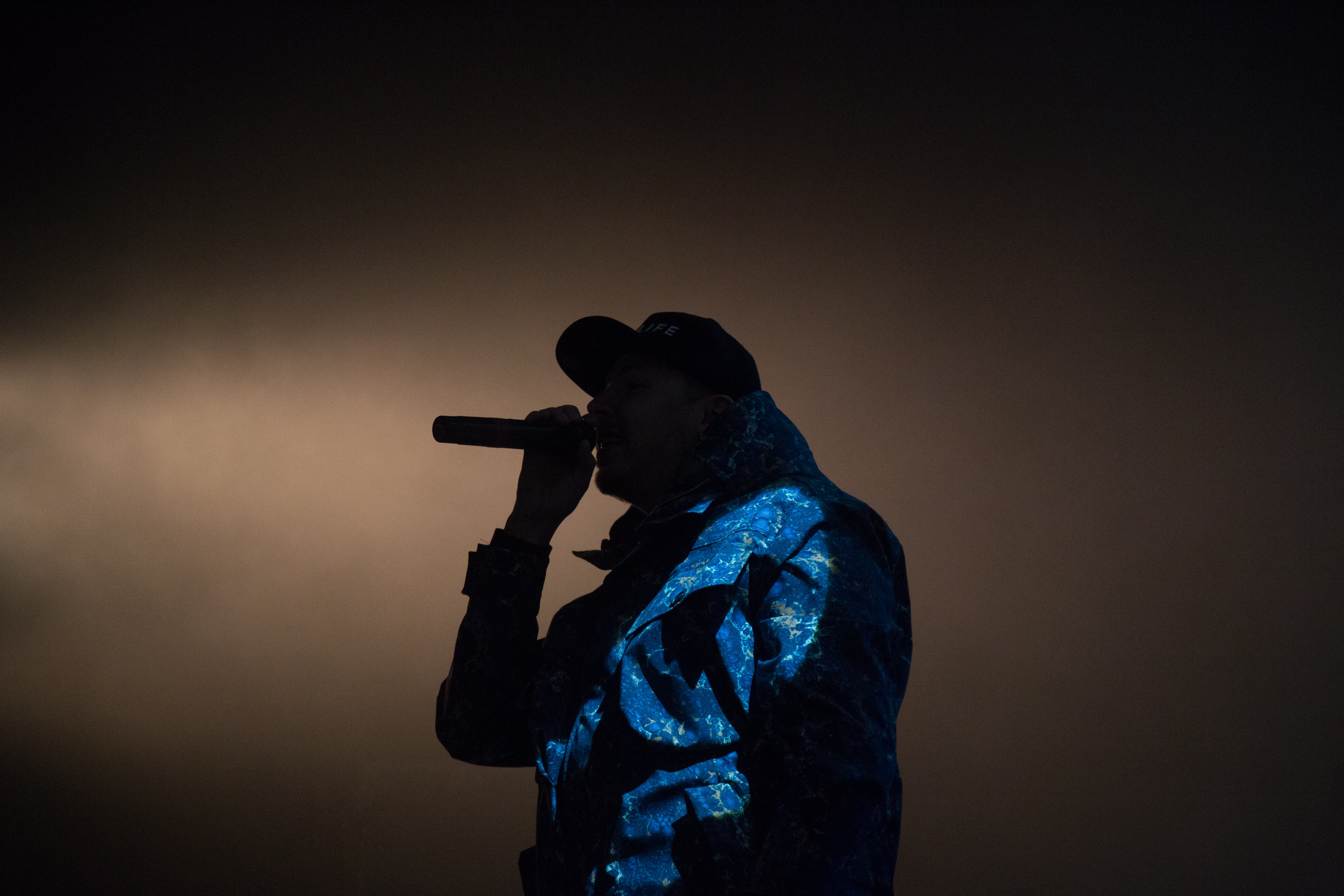 A silhouette of a musician in a cap performing with a microphone against pale smoke in the background