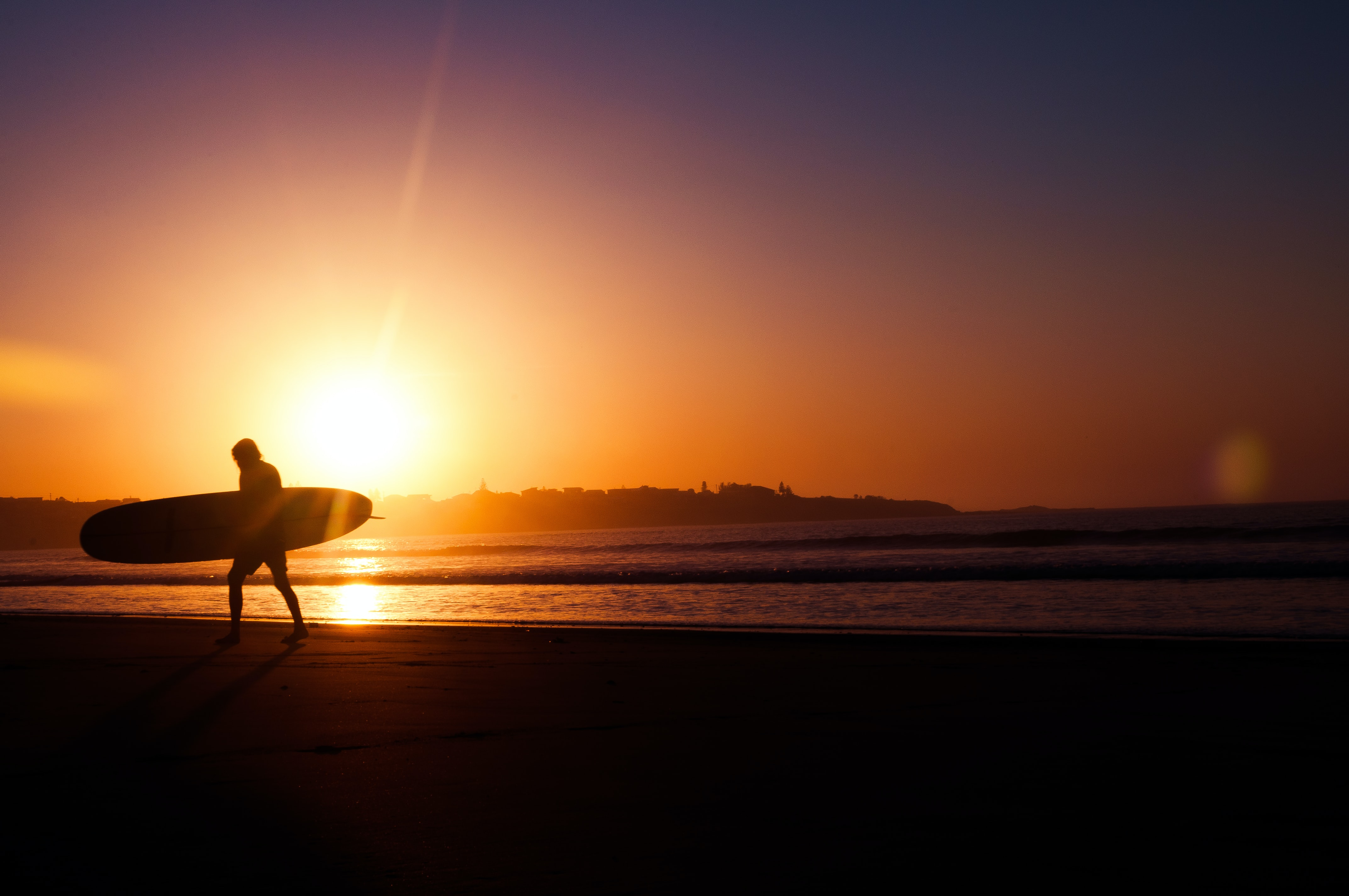 A silhouette of a man walking along the shore as the sun sets over the horizon at Seven Mile Beach