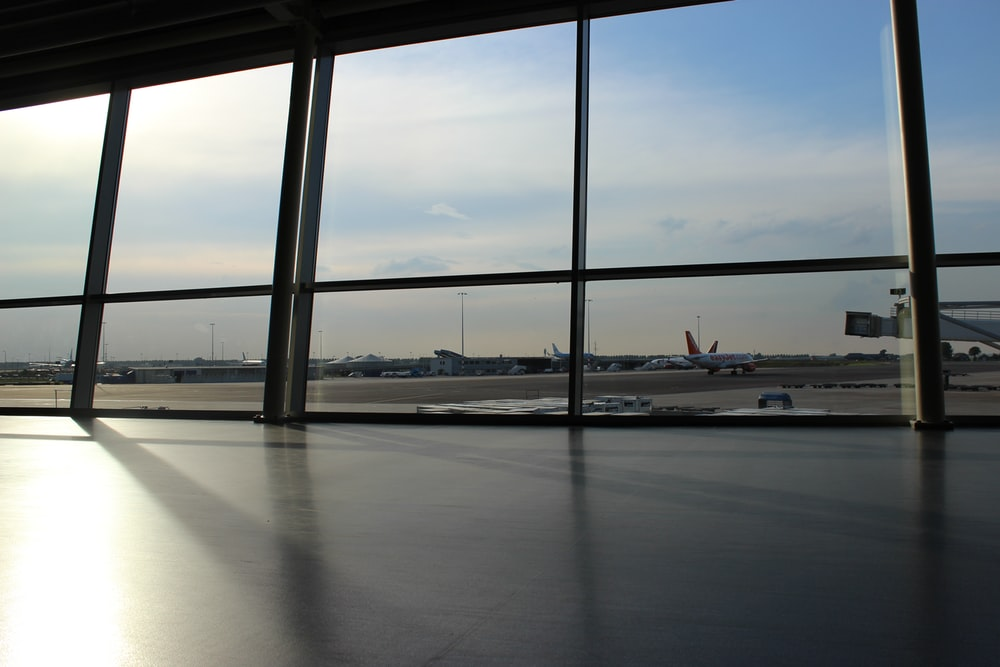 glass panel window showing airplanes and runway under blue sky during daytime