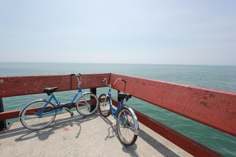 two bicycle parked beside red raiols