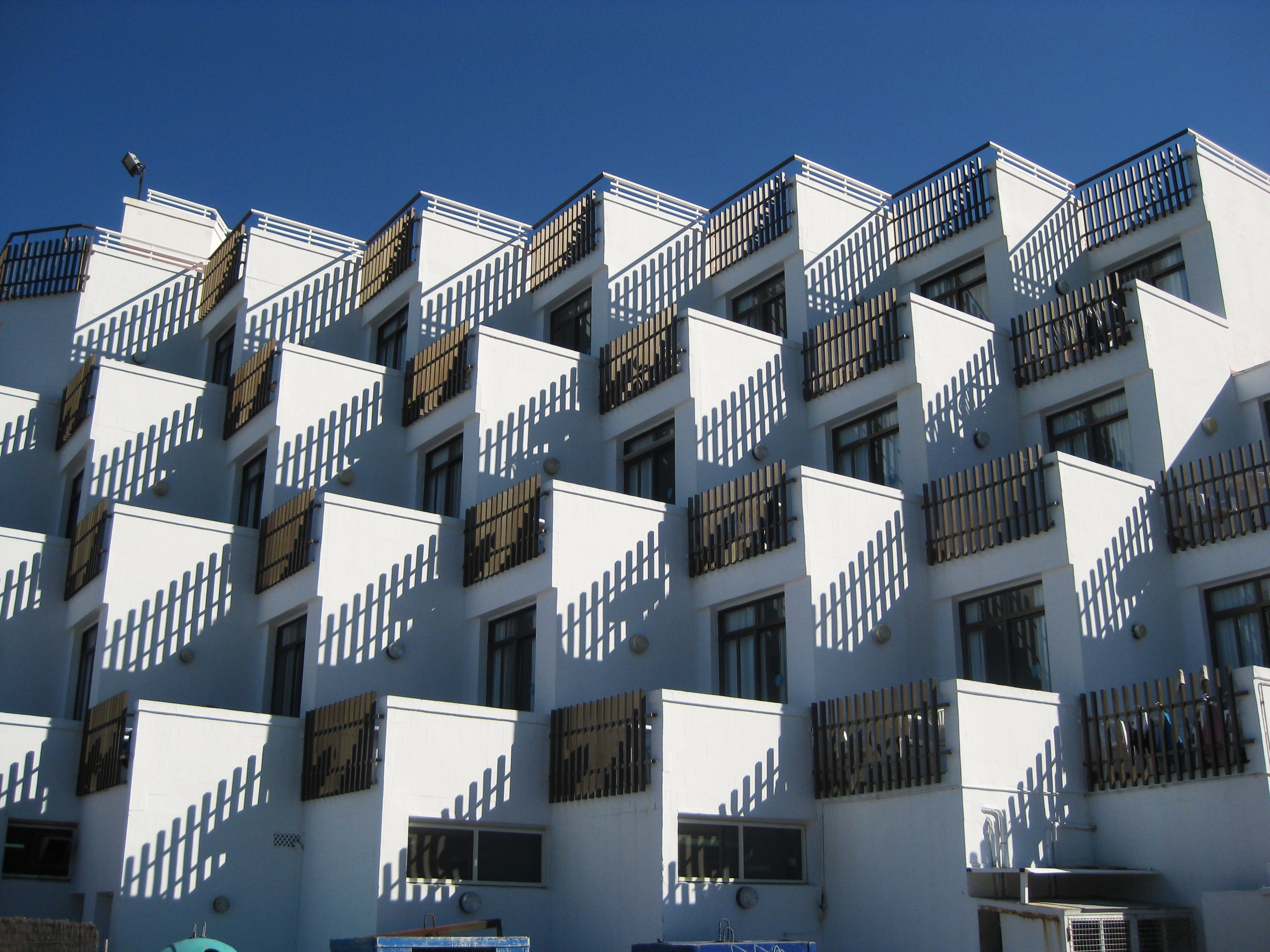 Regular rows of small terraces in a white residential building