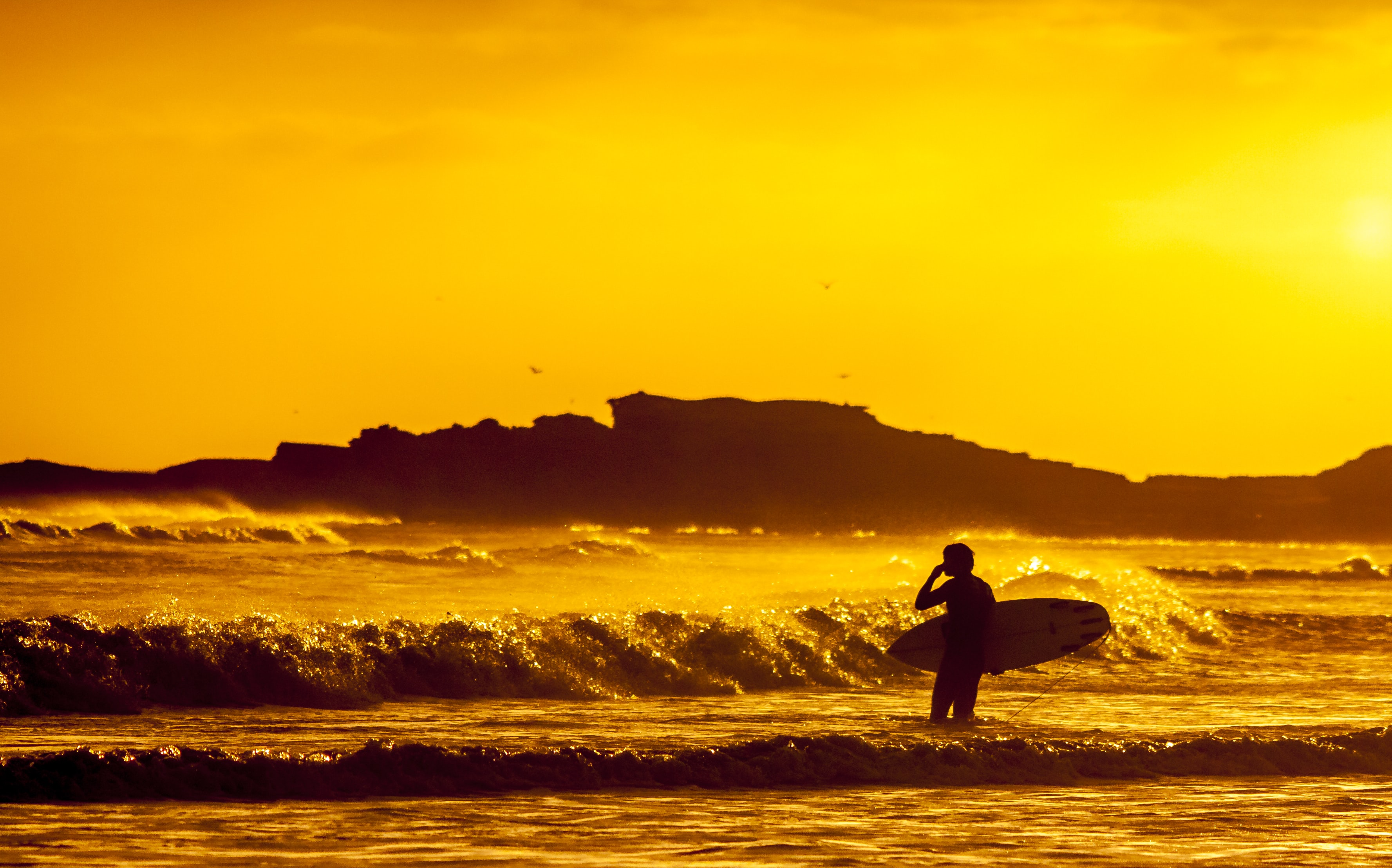 A surfer stood in the sea at sunset, holding a board beneath a vibrant orange dusk sky