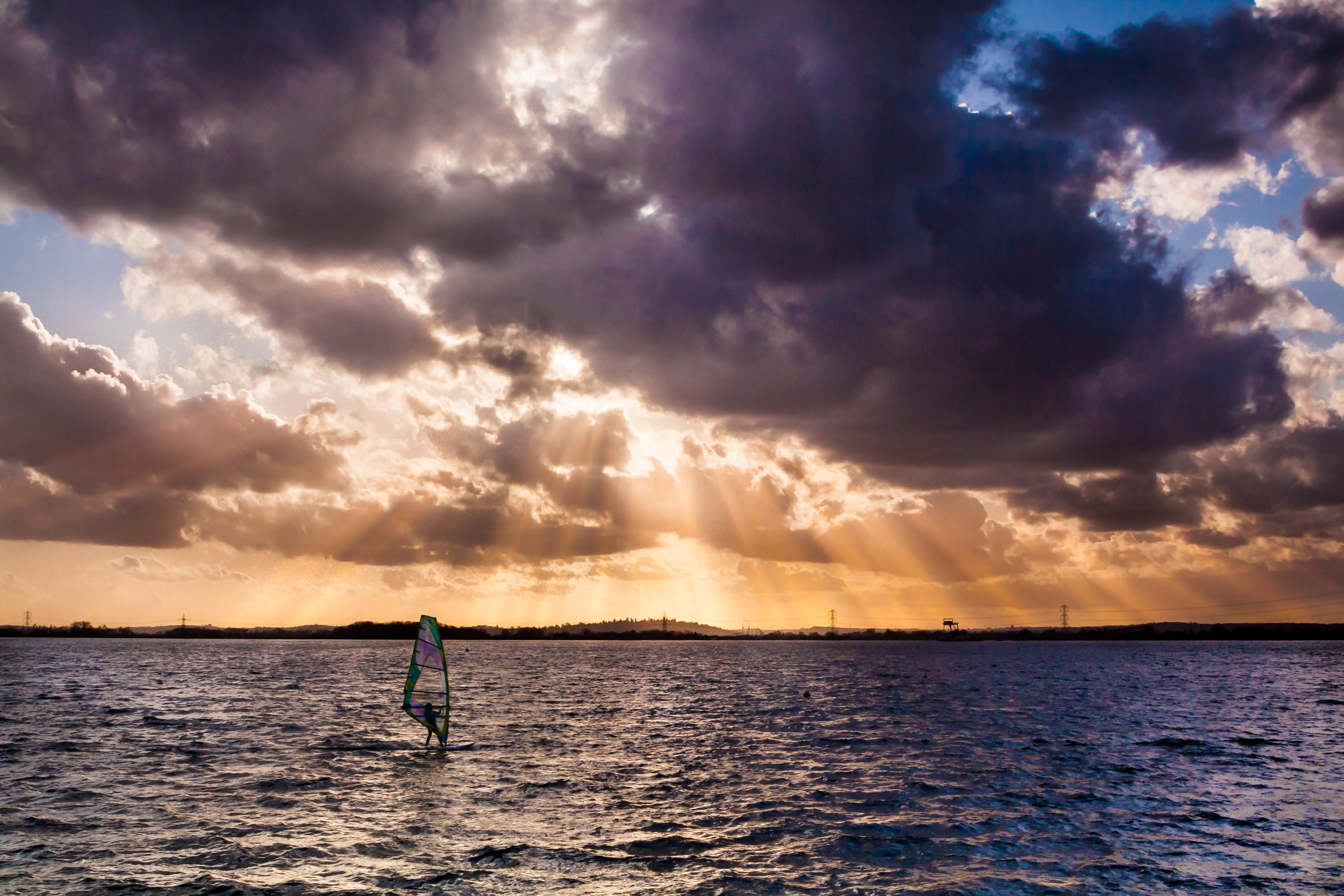 A windsurfer on a lake during sunset