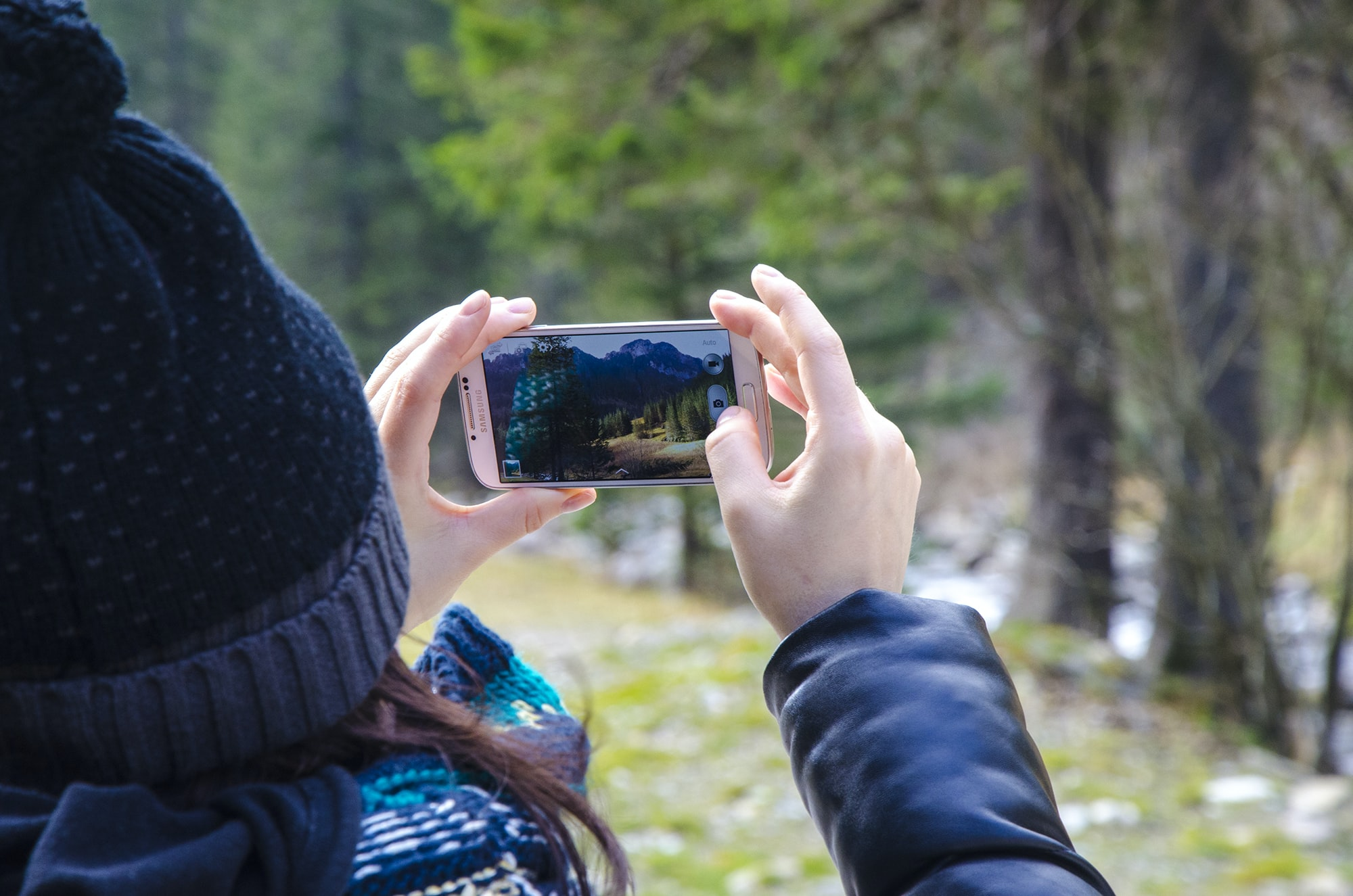 A woman taking a photo of the forest with an iPhone Cellphone