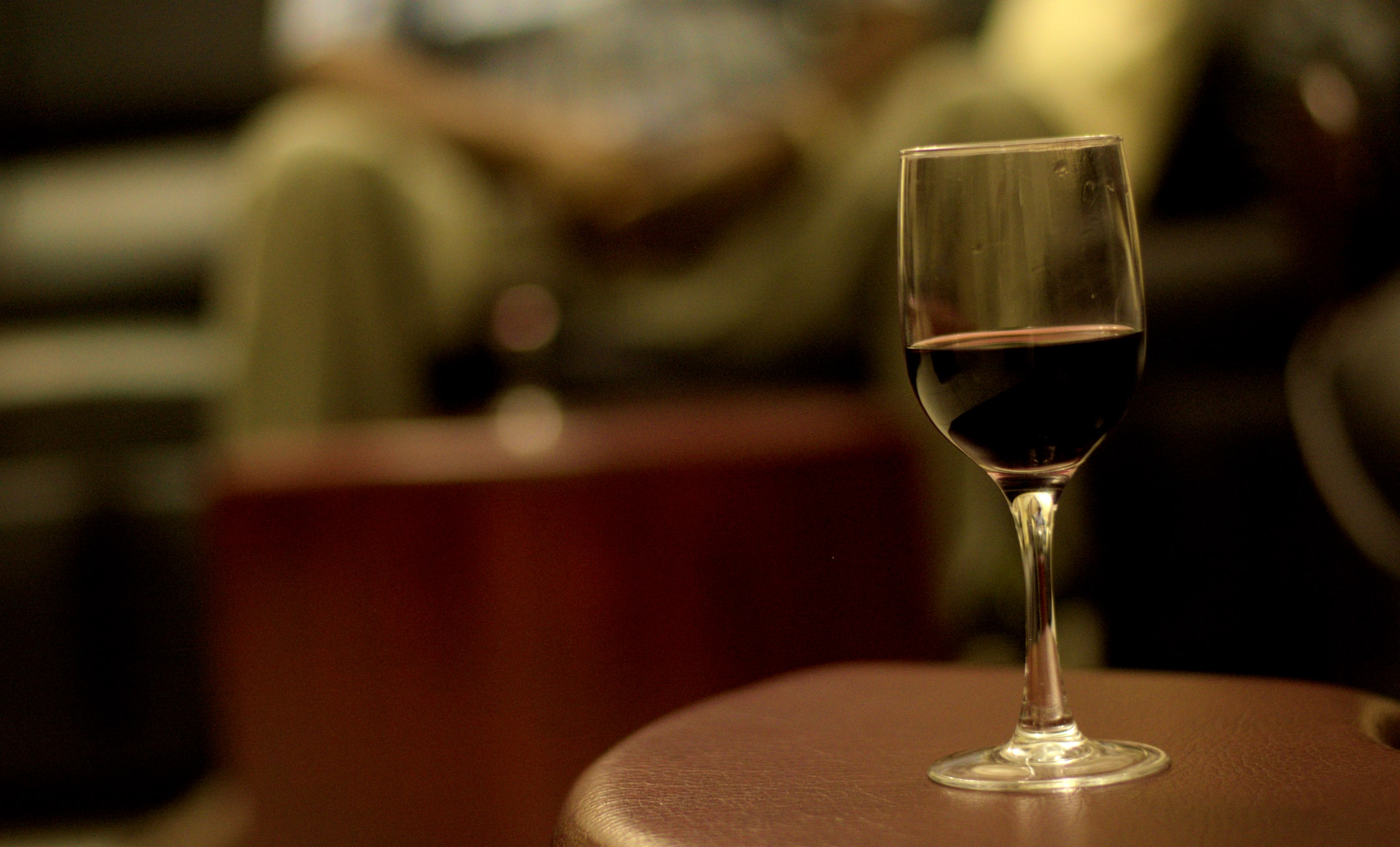 A single glass of red wine on a bar table.