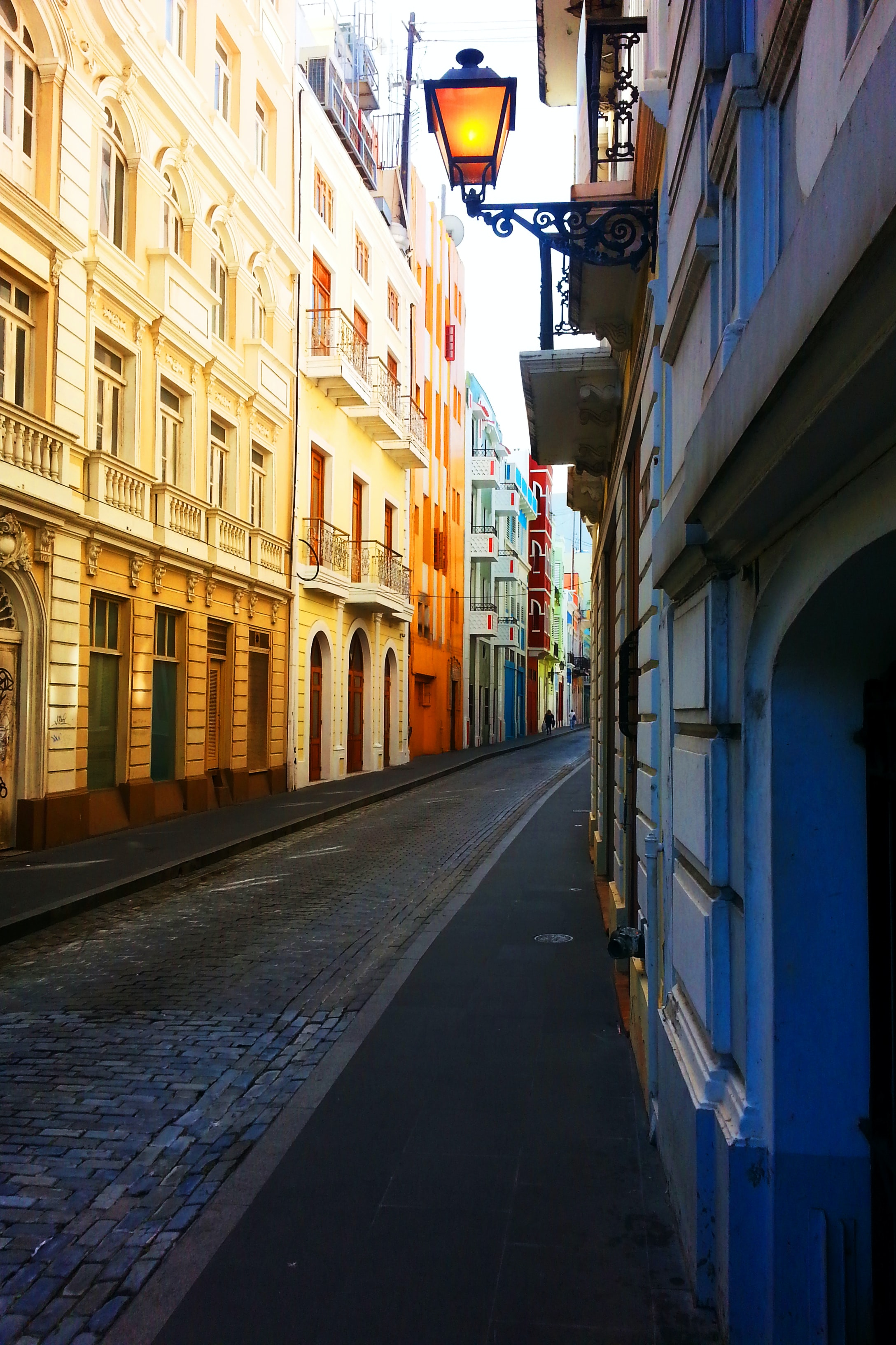 Alleyway with colorful bright buildings flanking the road with a lit lamp protruding from a house