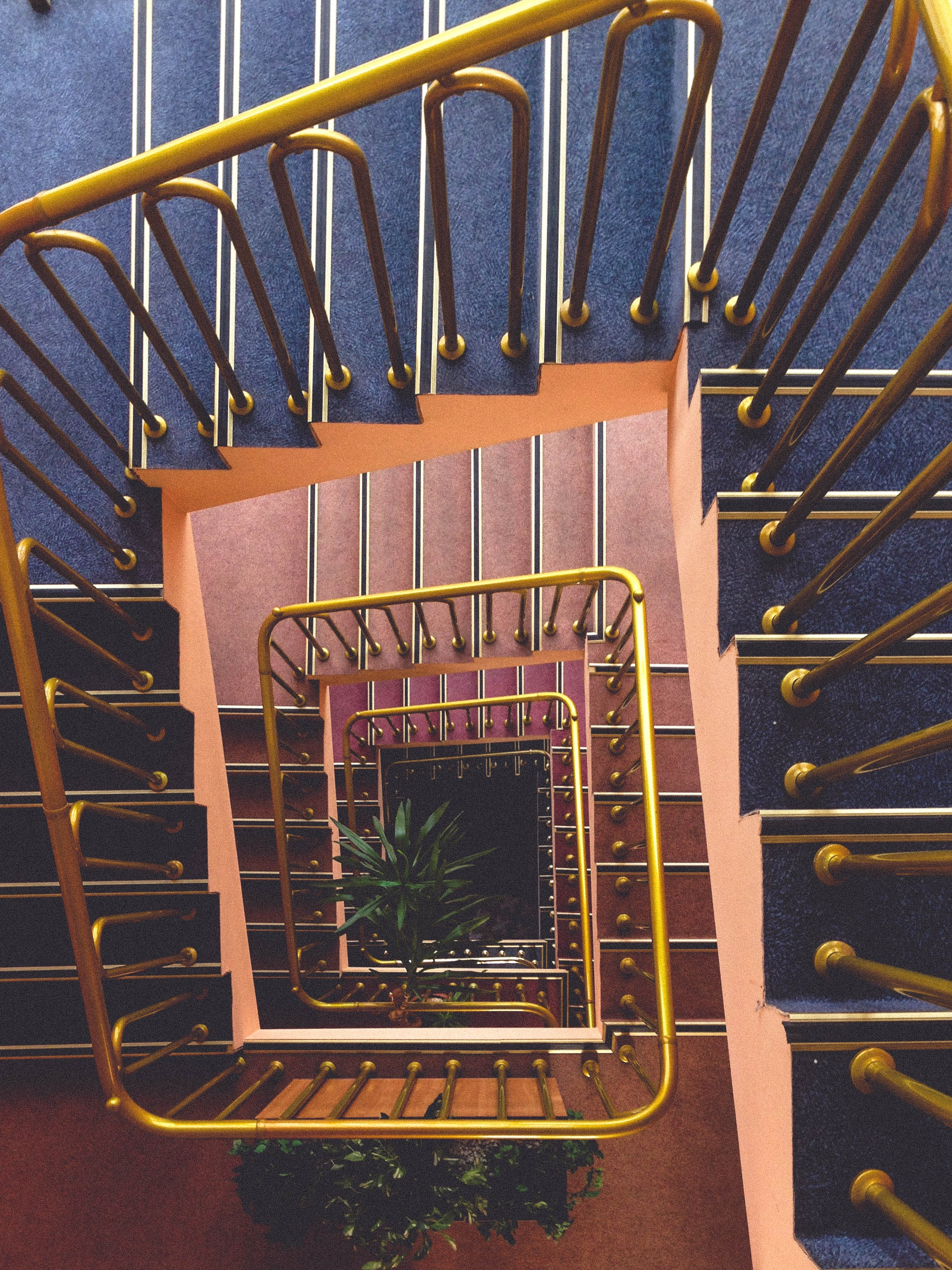 Looking down at a vintage spiral staircase with a gold banister