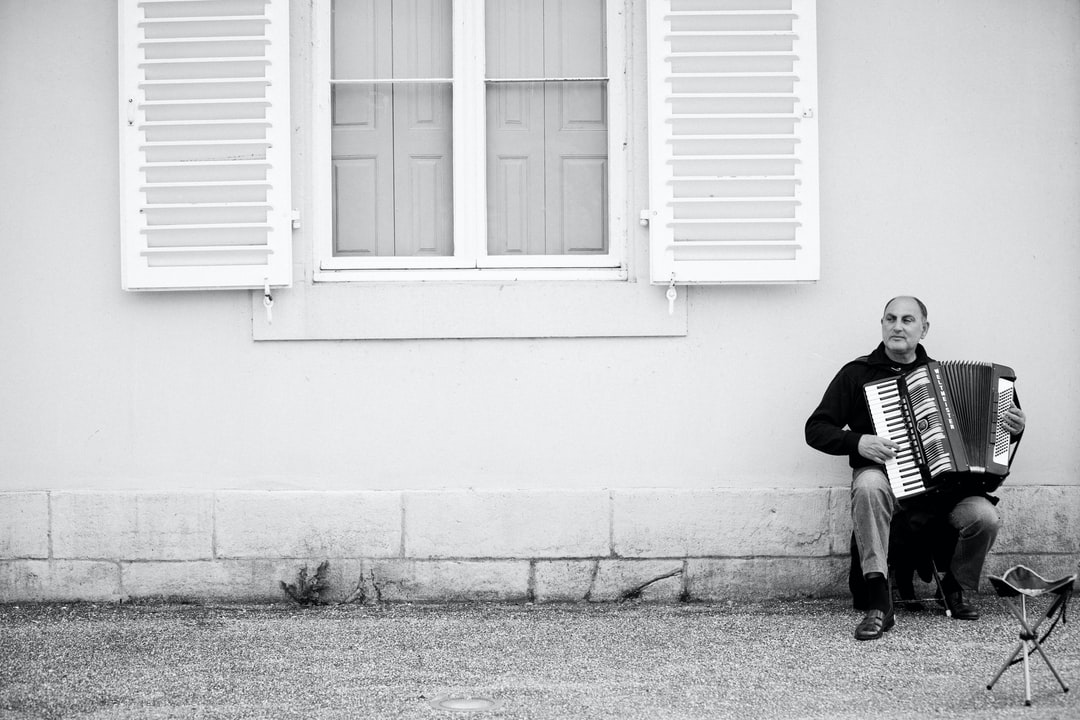 Accordionist under a window in black and white