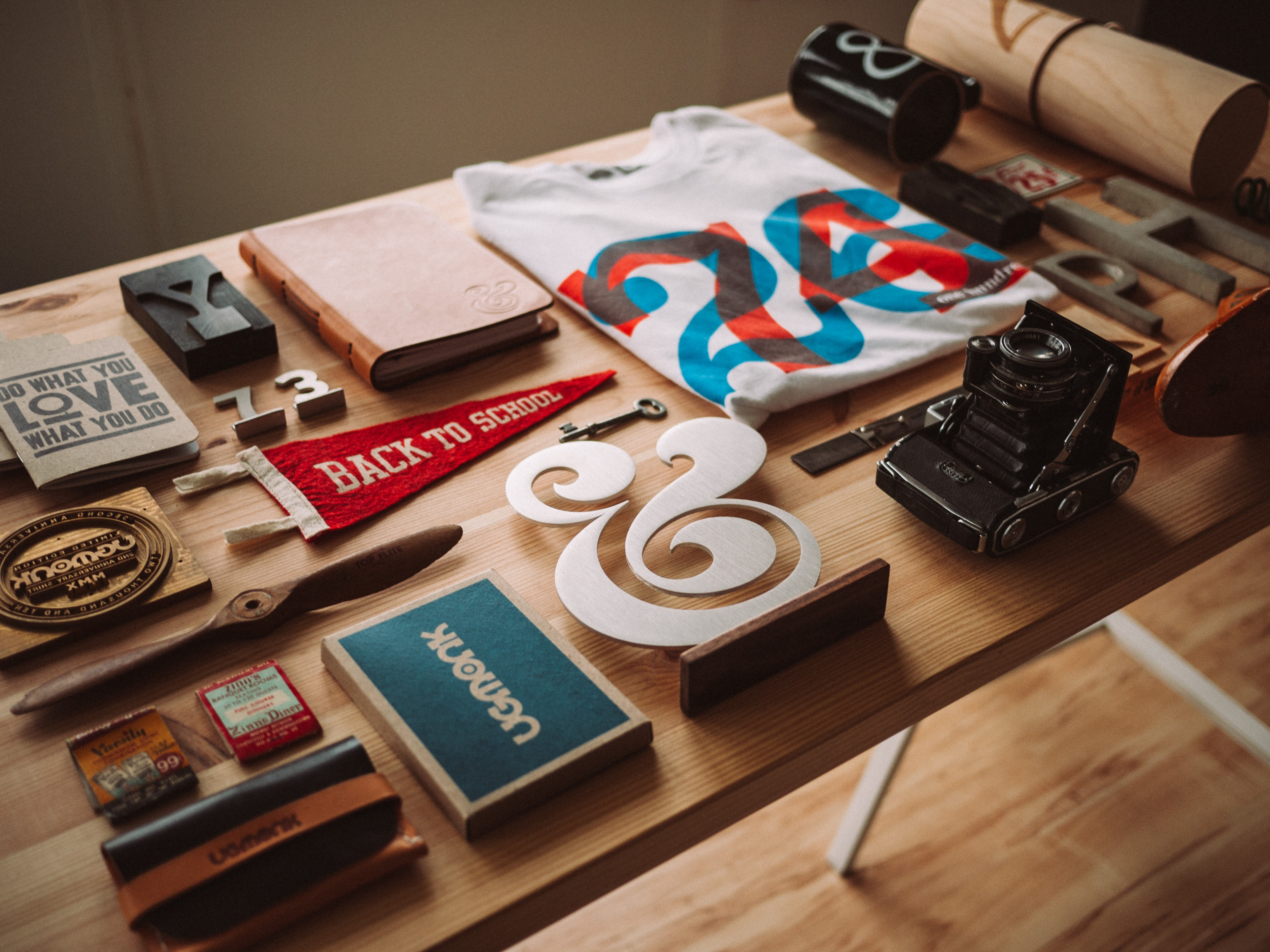 A flatlay with a t-shirt, a camera, a notebook and various trinkets on a table