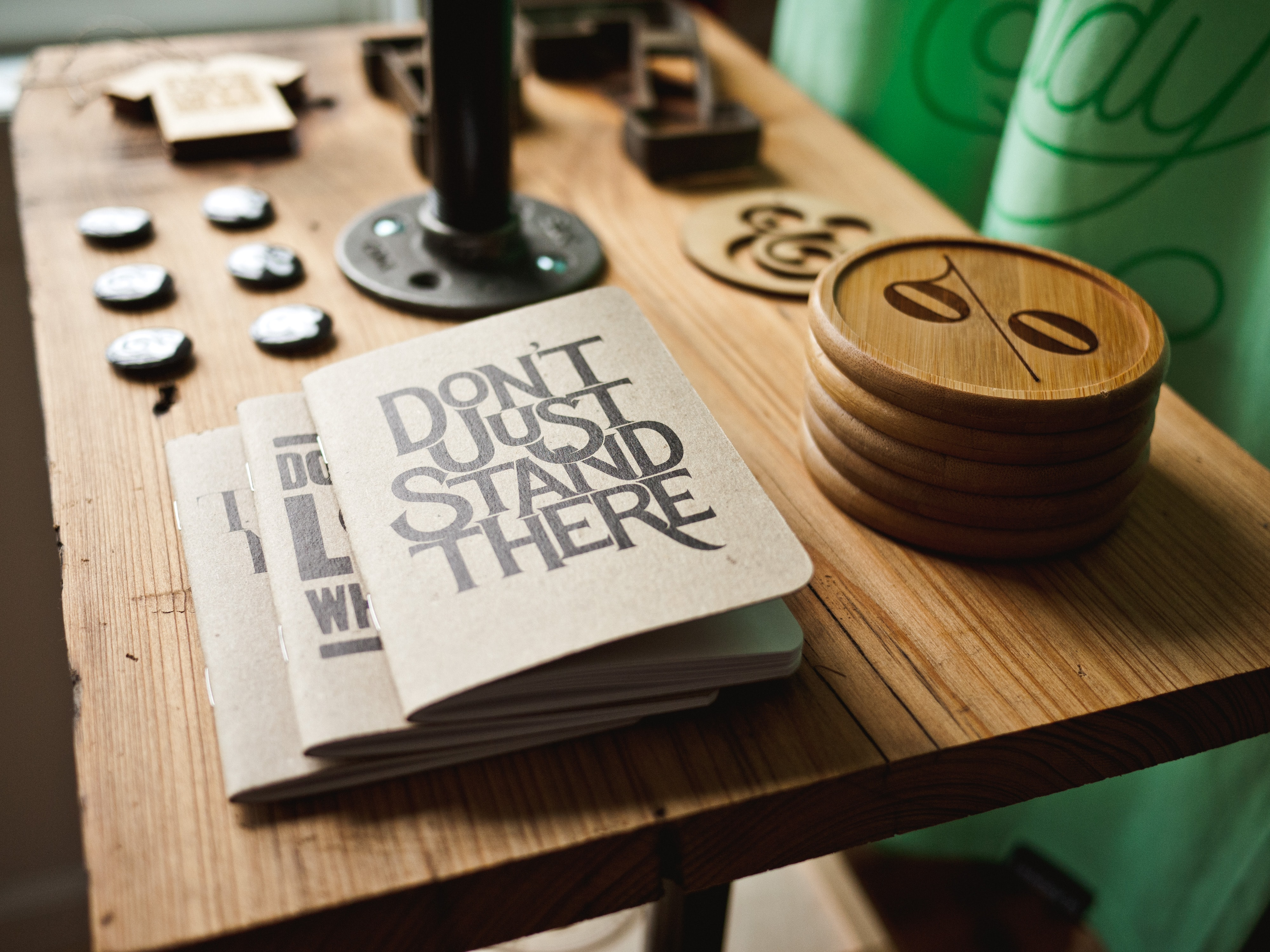 "Notebooks with a ""don't just stand there"" cover on a table next to various trinkets"