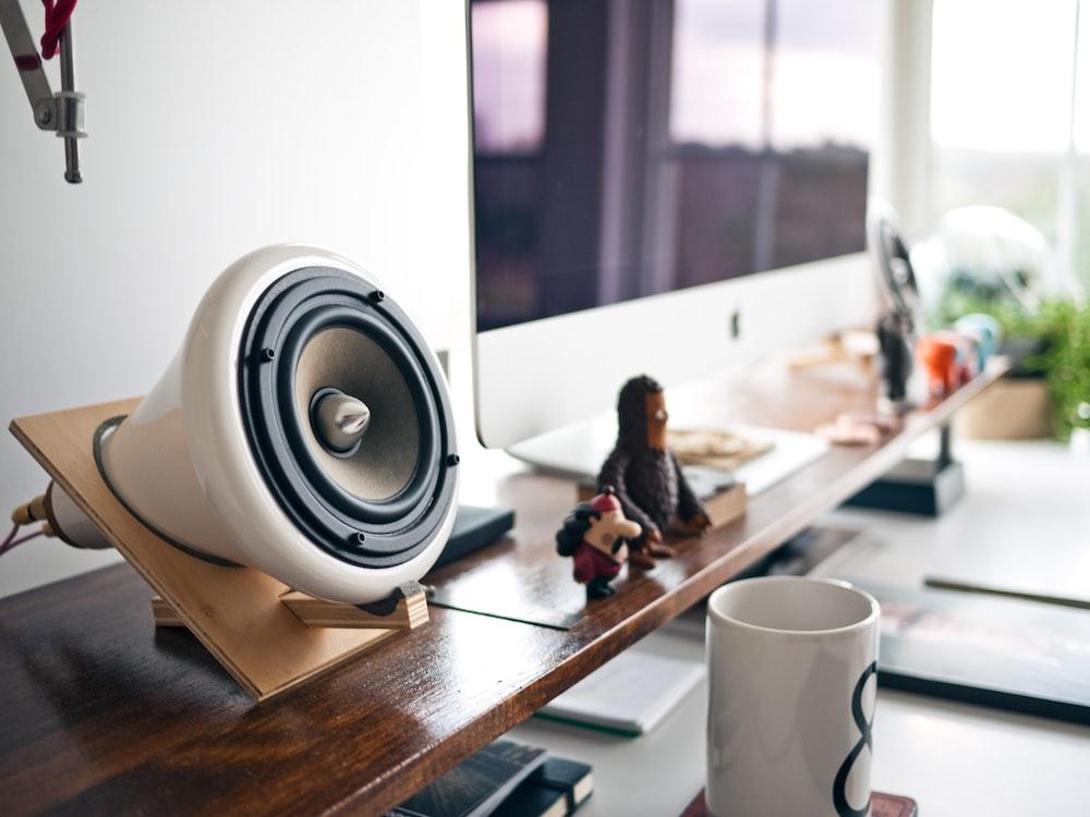 white speaker in brown holder beside silver Imac