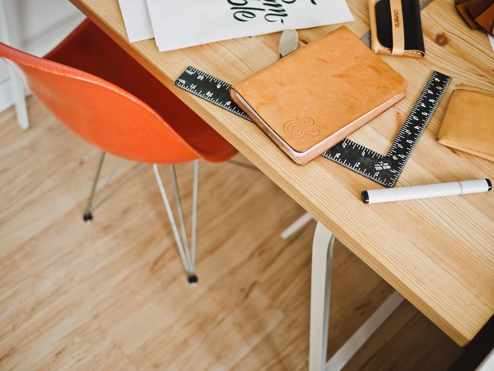 brown book on L-shape ruler beside pen