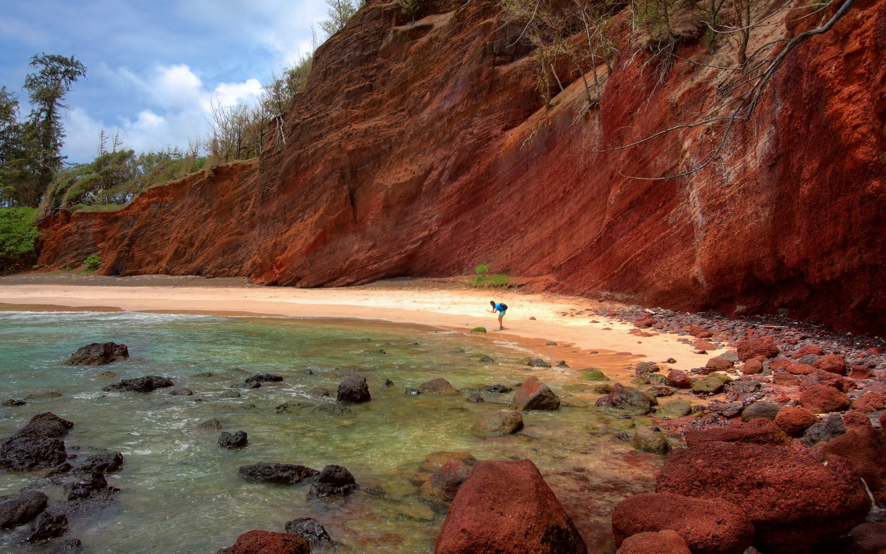 A person standing on a rocky beach under a steep red rock face