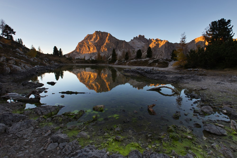 water mirror reflection of mountain during golden hour