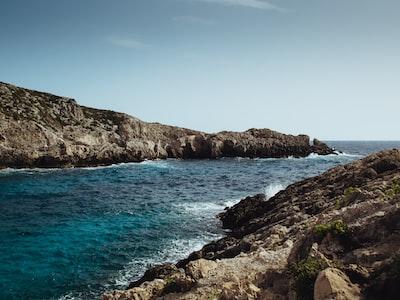 brown rock formation near sea mediterranean teams background