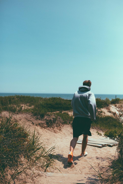 man walking on brown sand