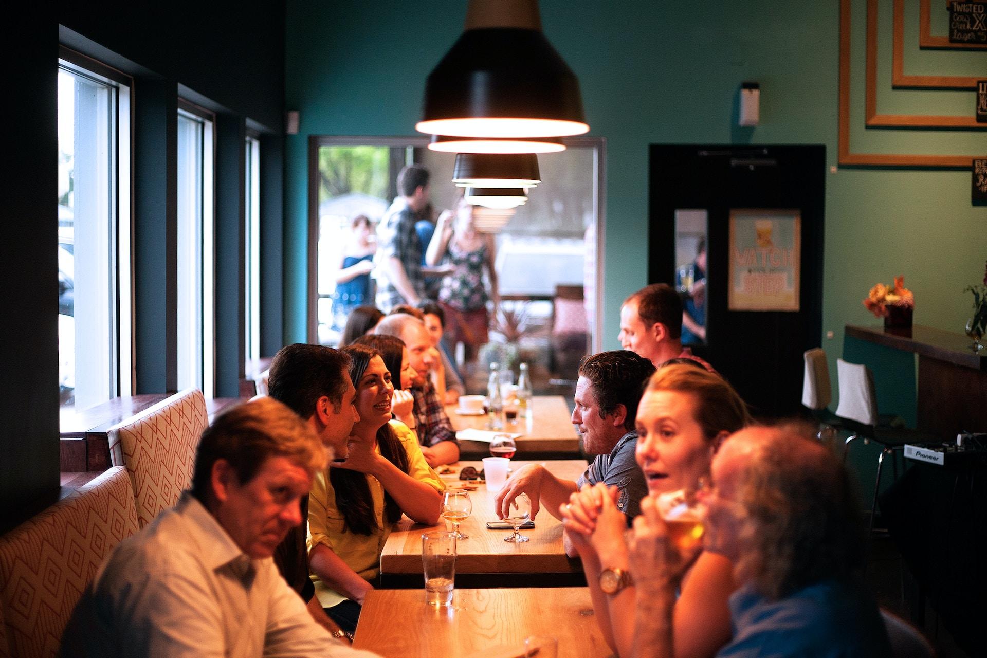 people sitting beside brown wooden table inside room