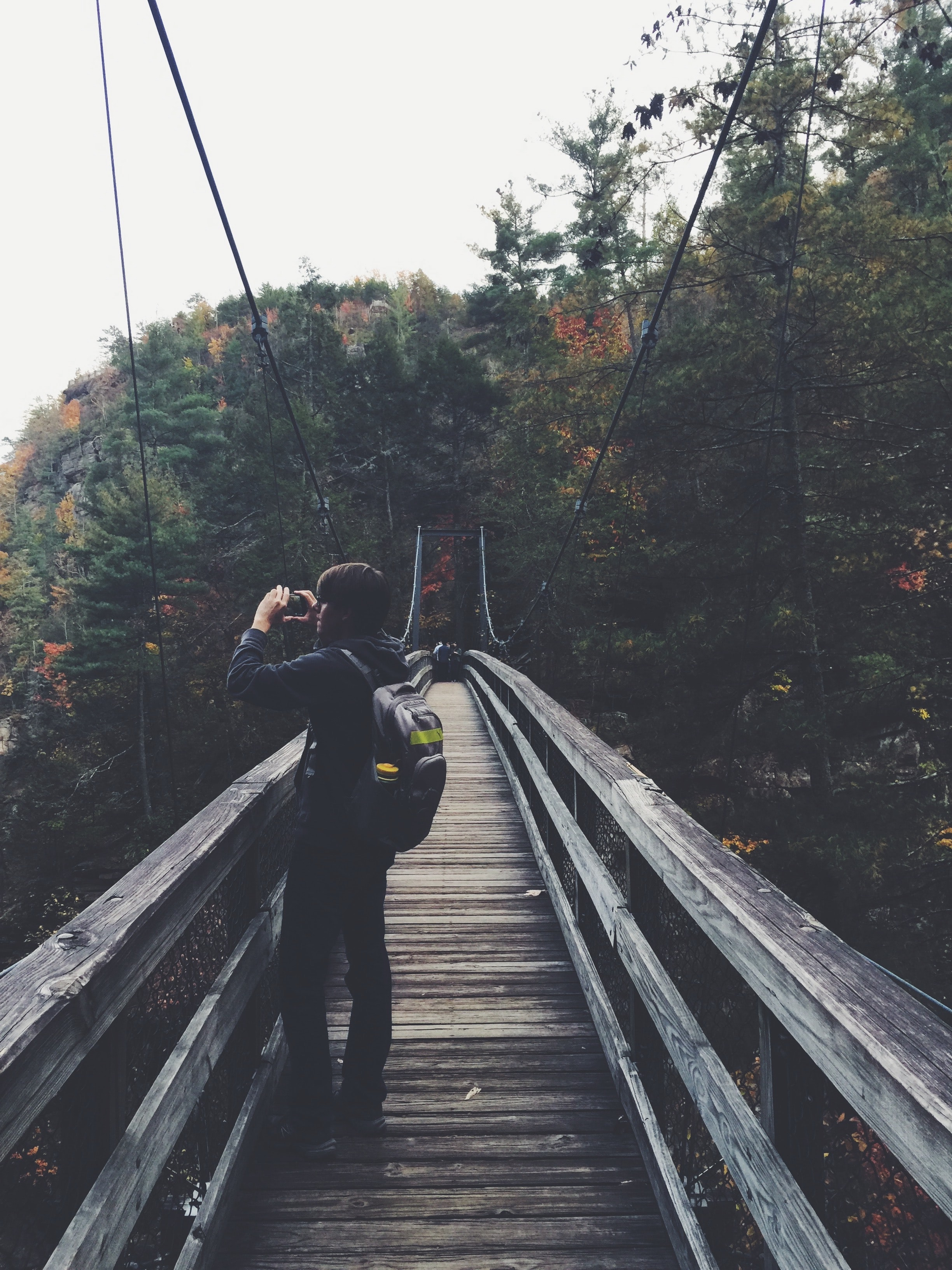 A man in dark casual clothing wearing a gray bag standing on a wooden suspension bridge in an early autumn forest taking a picture of the scenery