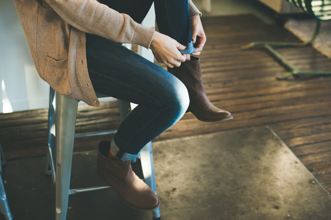 A girl sitting on a stool wearing brown booties, denim jeans, and a brown sweater