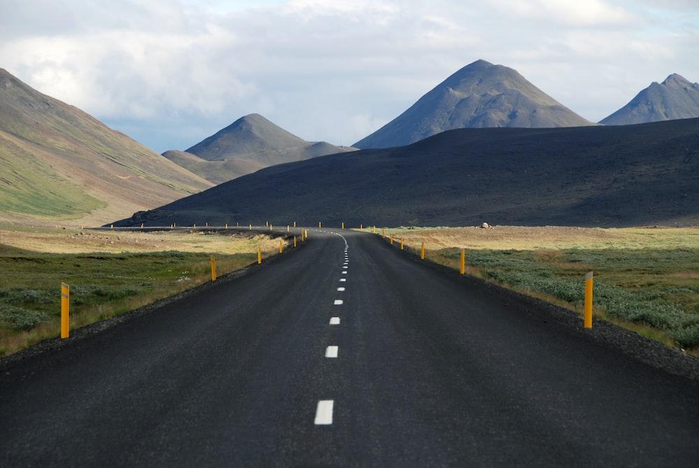black asphalt road between grass field
