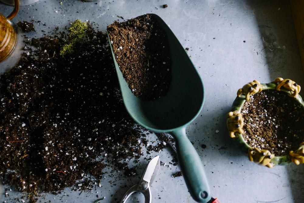 green metal garden shovel filled with brown soil