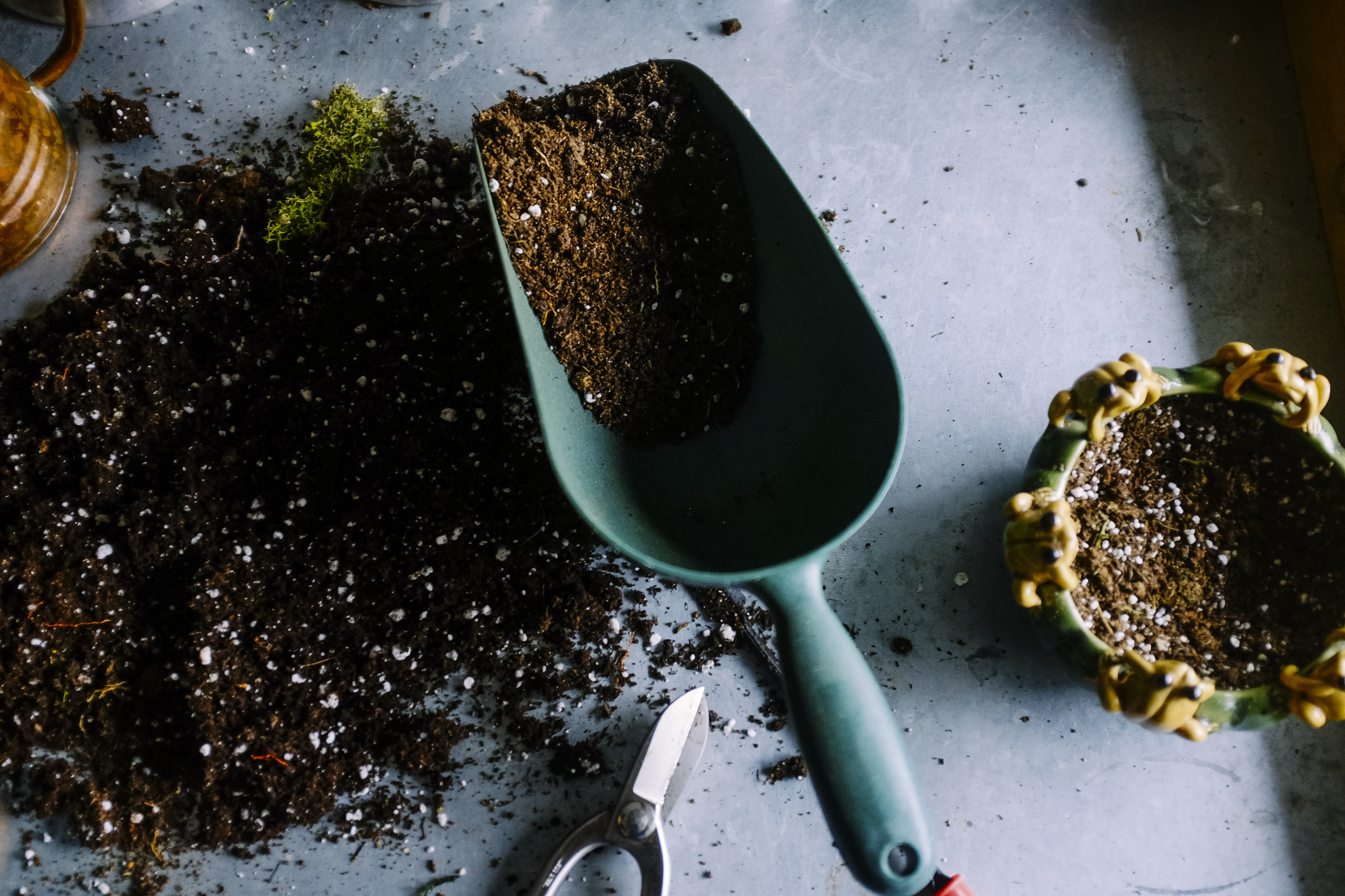 green metal garden shovel filled with brown soil