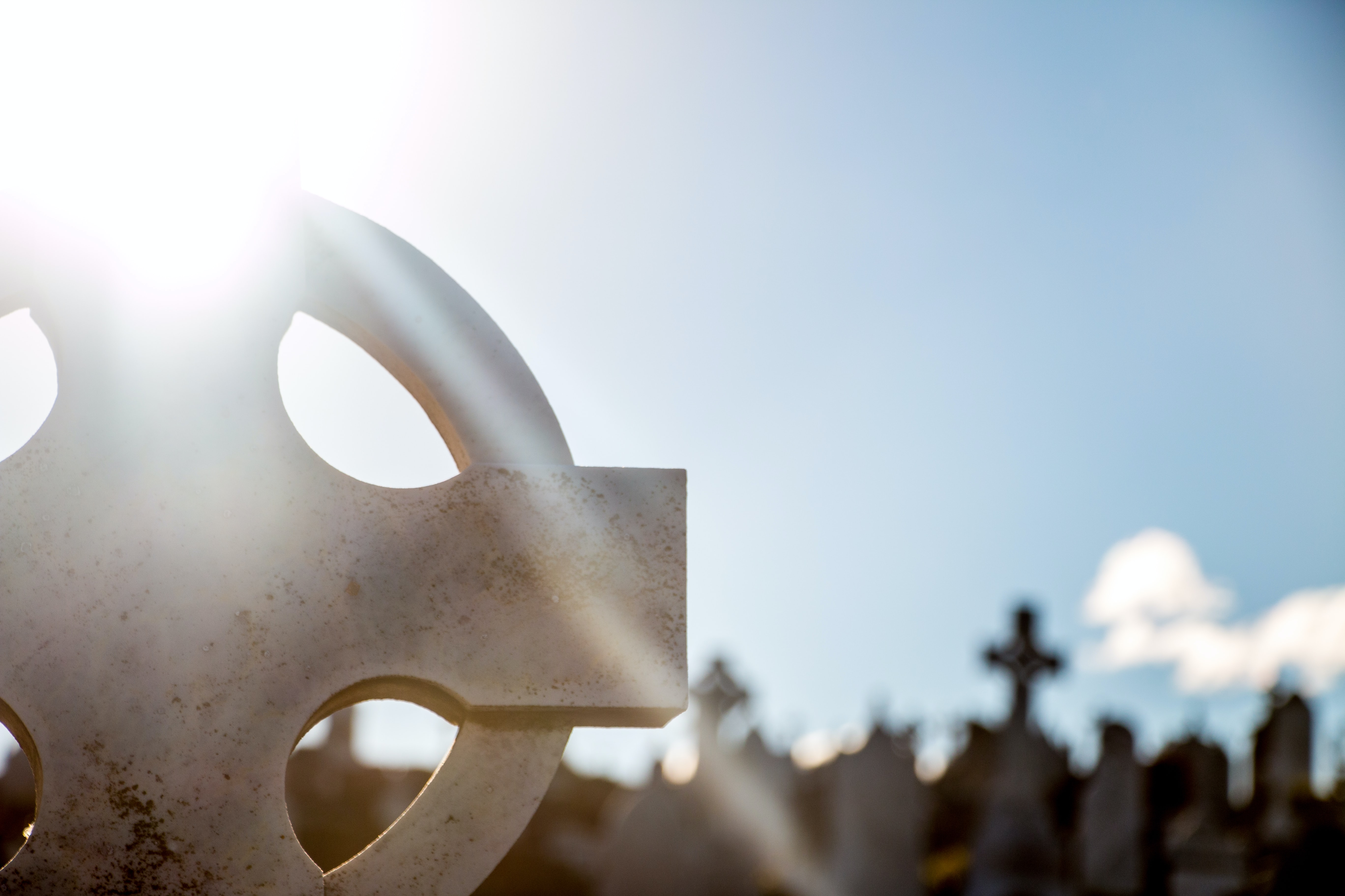 Sunbeams shine over a cross tombstone in a graveyard