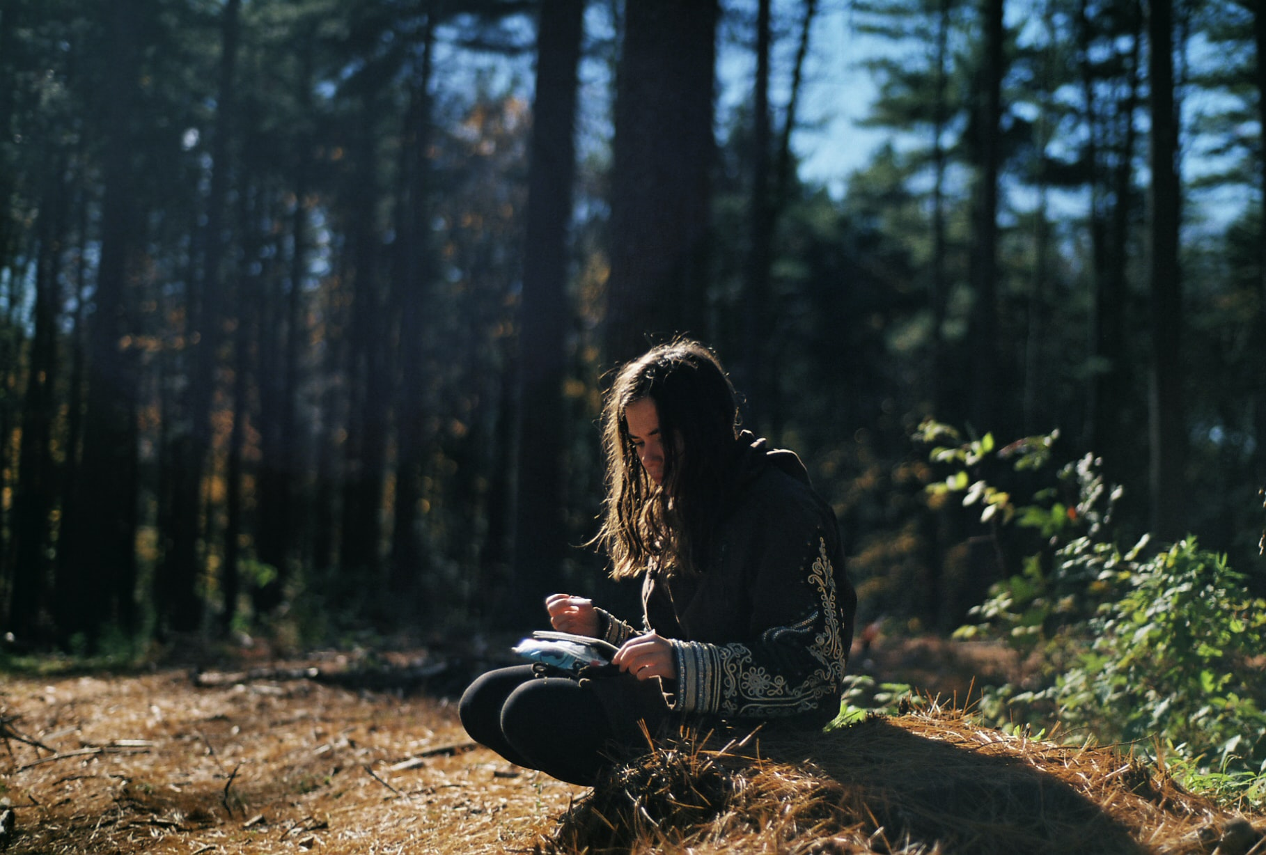 A pensive dark-haired girl crouching on the forest floor journaling