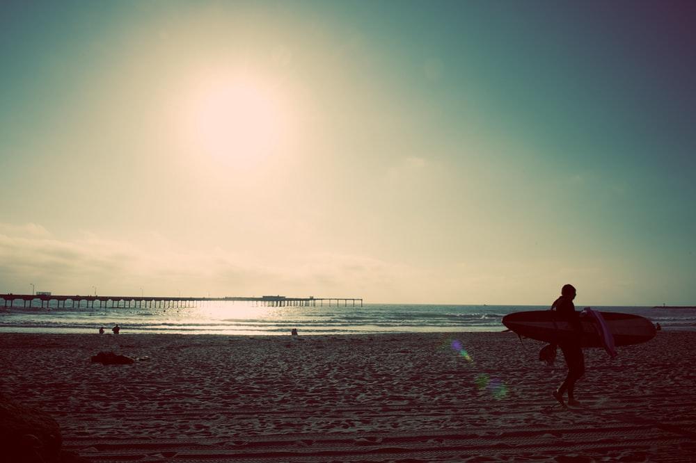 person carrying surfboard near seashore